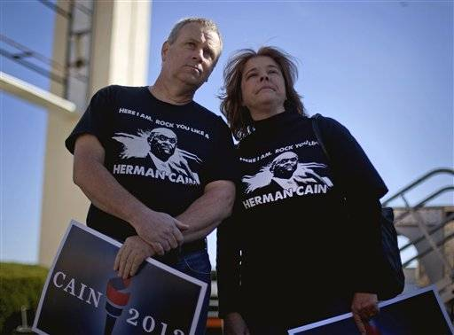 Andy, left, and Cathy Deignan, of Locust Grove, Ga., wait for Republican presidential candidate Herman Cain's campaign event to start at his new state headquarters Saturday, Dec. 3, 2011, in Atlanta, Ga. Cain is keeping supporters in suspense ahead of his expected announcement Saturday about whether he will quit the race after a string of sexual harassment allegations and a claim of an extramarital affair.