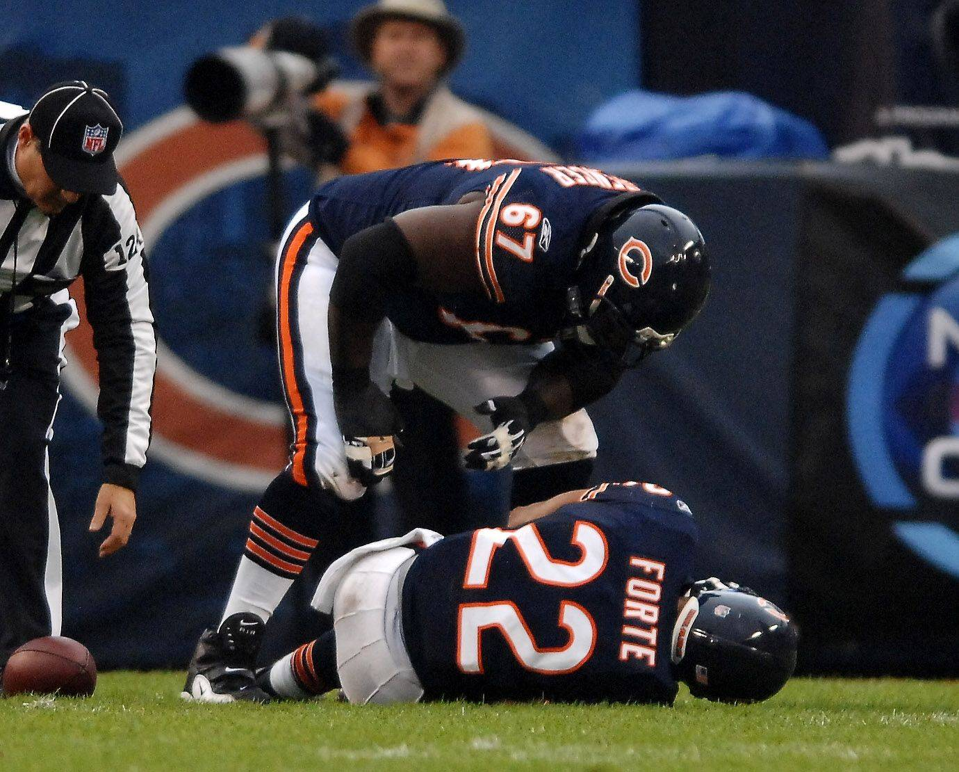 Chris Spencer checks on running back Matt Forte, who injured his right knee in the first quarter and did not return Sunday.