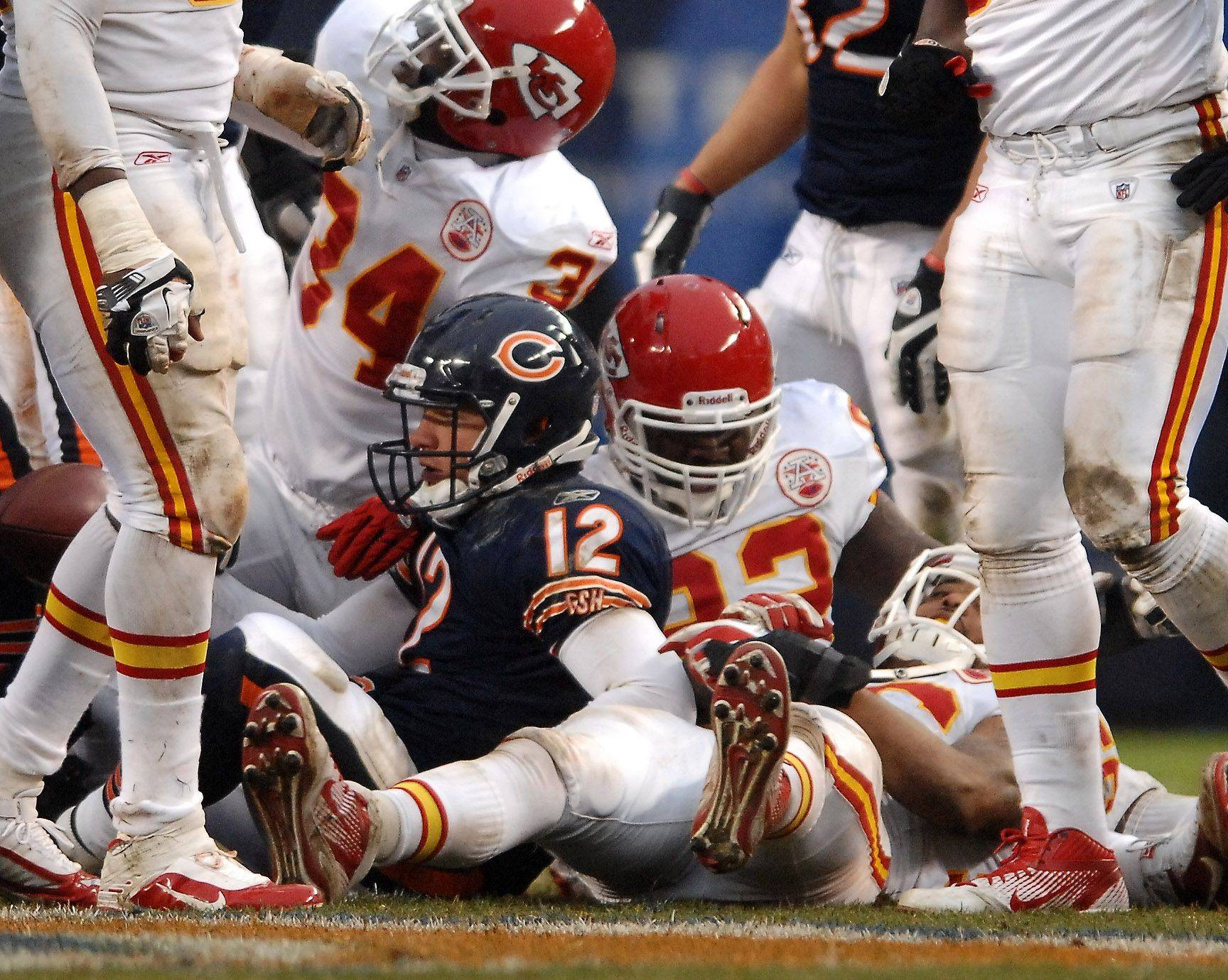 Chicago Bears quarterback Caleb Hanie (12) sits in a pile of Kansas City defenders after a fourth quarter sack during Sunday's game at Soldier Field in Chicago.