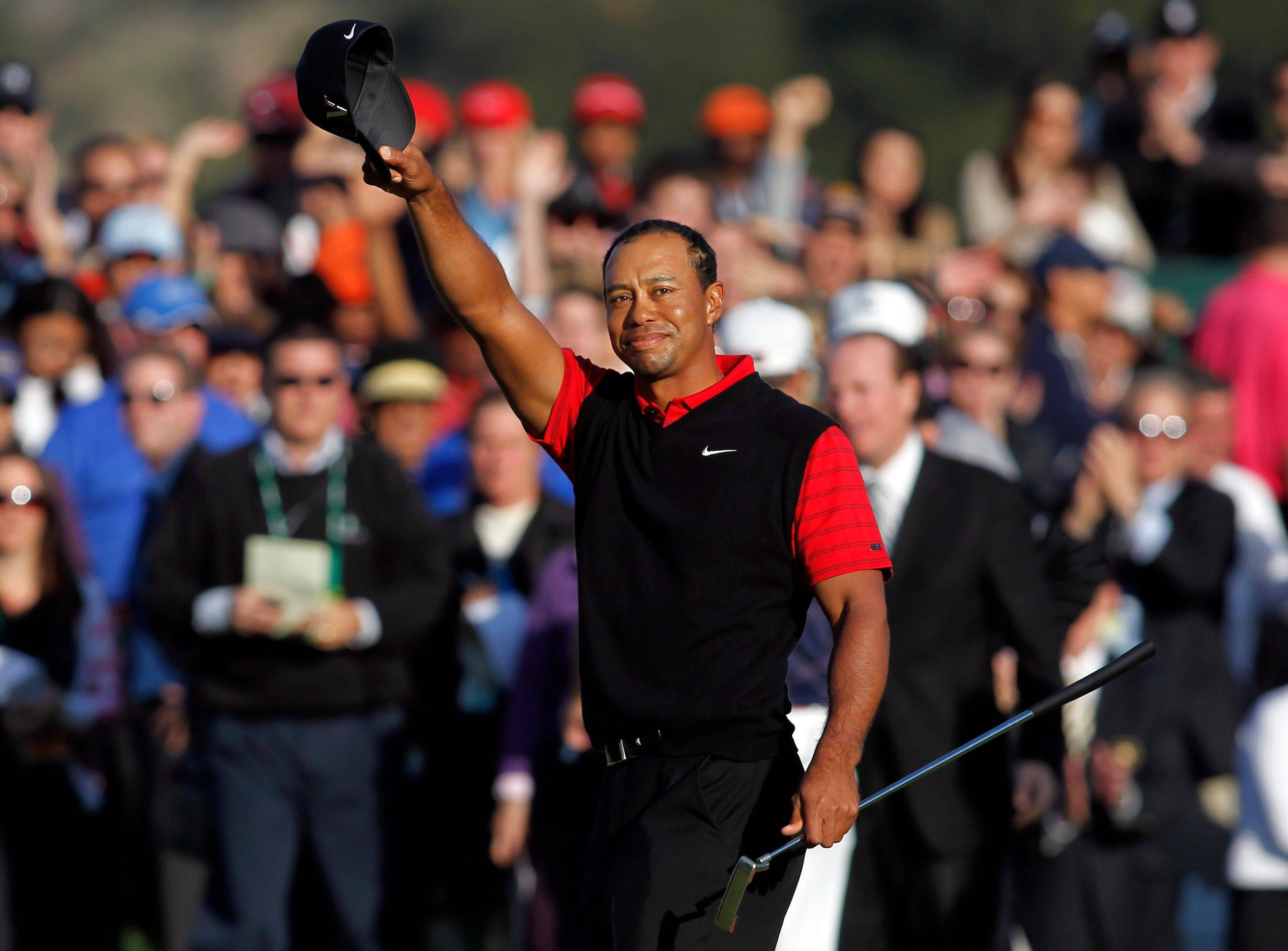 Tiger Woods waves his cap Sunday after winning the Chevron World Challenge golf tournament at Sherwood Country Club in Thousand Oaks, Calif.