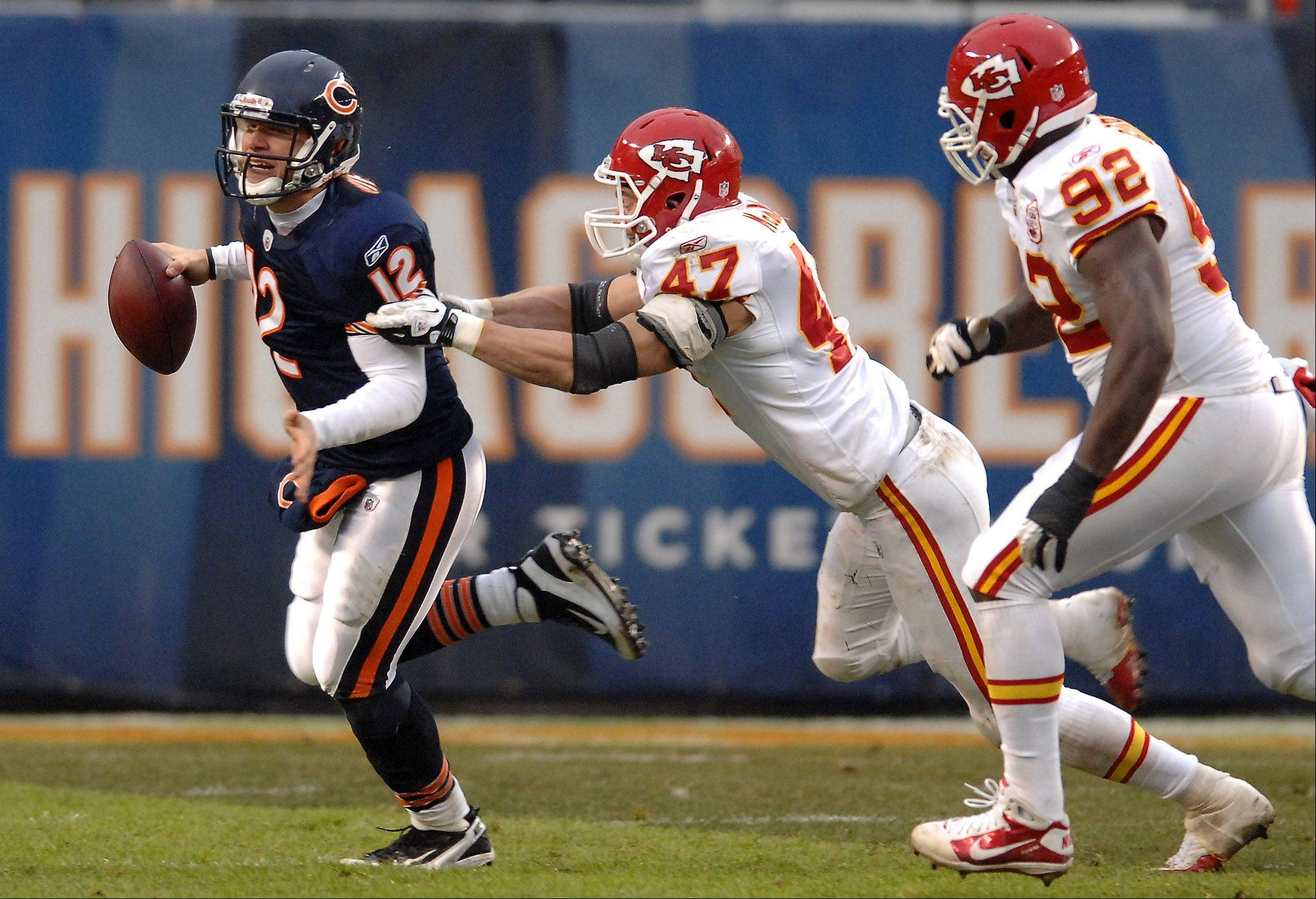 Rick West/rwest@dailyherald.comChicago Bears quarterback Caleb Hanie (12) is pursued by Kansas City Chiefs strong safety Jon McGraw (47) and defensive end Wallace Gilberry (92) during Sunday's game at Soldier Field in Chicago. Gilberry eventually brought him down for a loss.