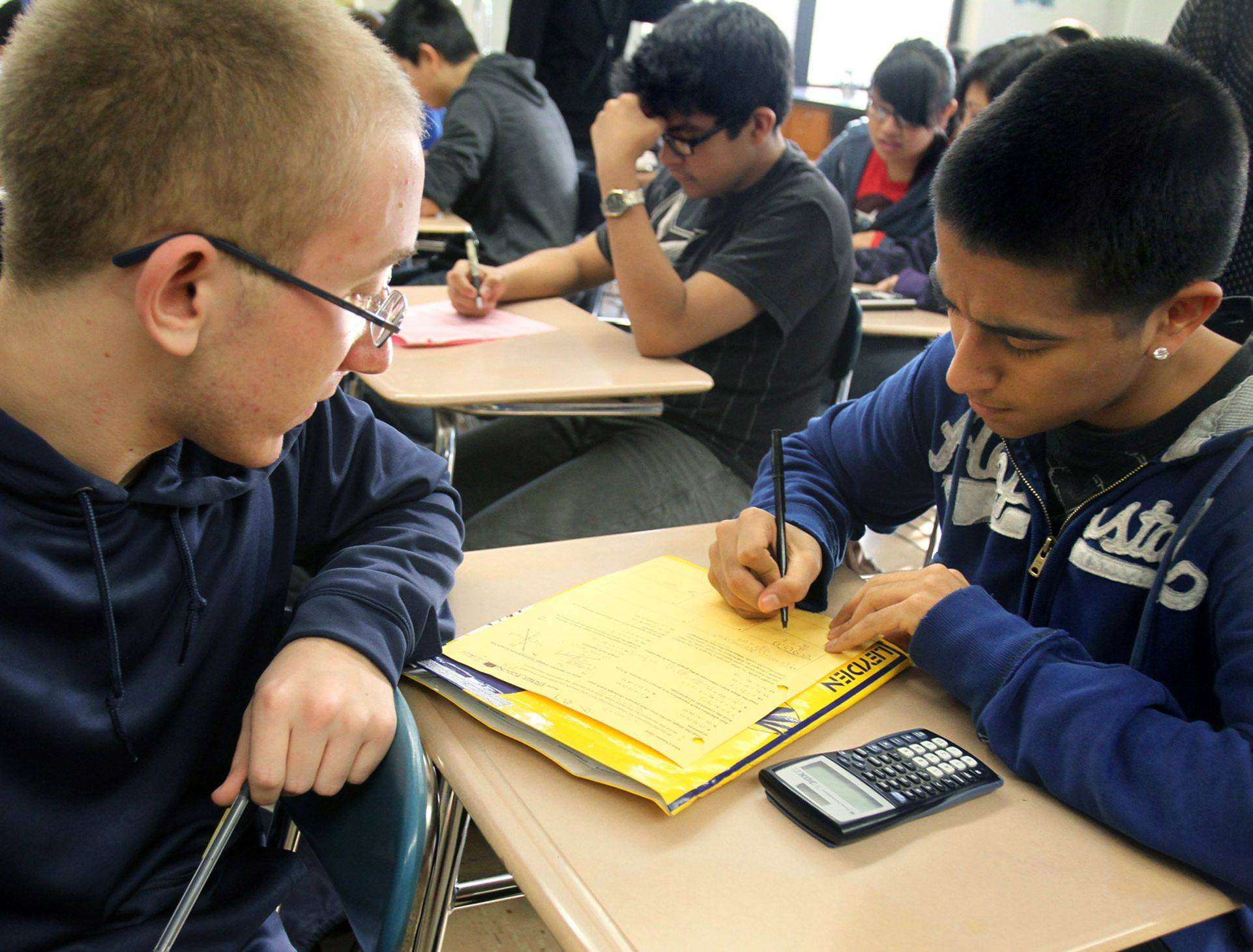 Robert Woods, a junior at West Leyden High School, left, mentors freshman Hector Herrera after school. The school, which ranks low in performance, isn't considering extending the day, but it does require freshmen and failing students to stay an extra 25 minutes.