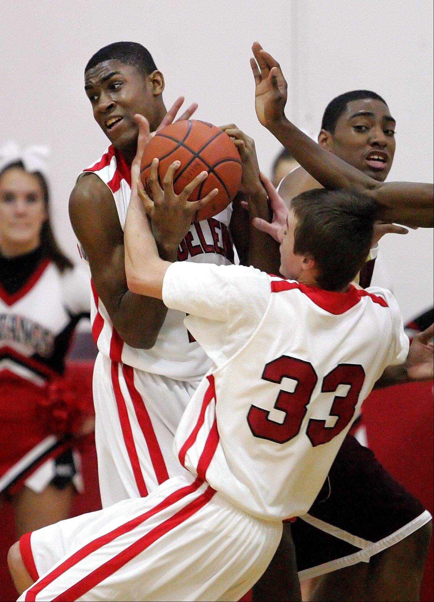 Mundelein's Chino Ebube, left, and Sean O'Brien battle for a rebound with Uplift's Corey Gonore during Monday's game at Mundelein High School.