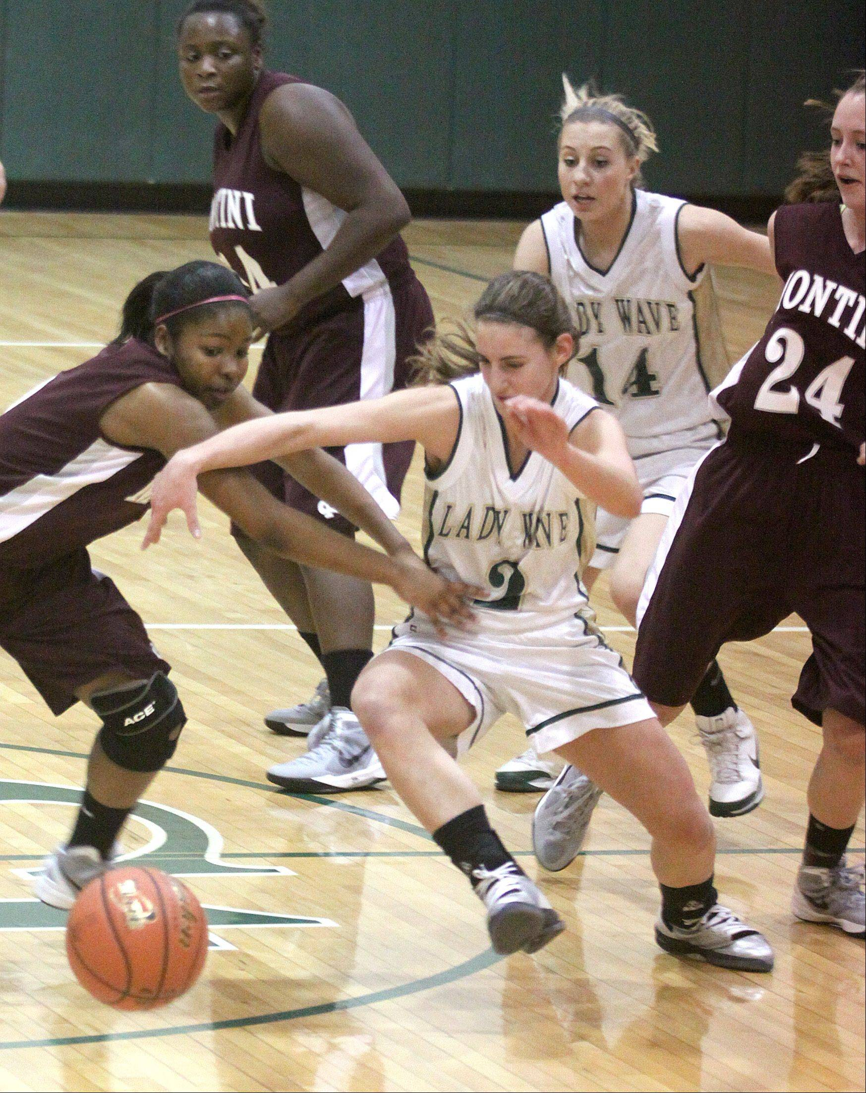 St. Edward's Rena Ranallo, right, and Montini's Nikia Edom, left, chase a loose ball during Tusday's girls basketball game in Elgin