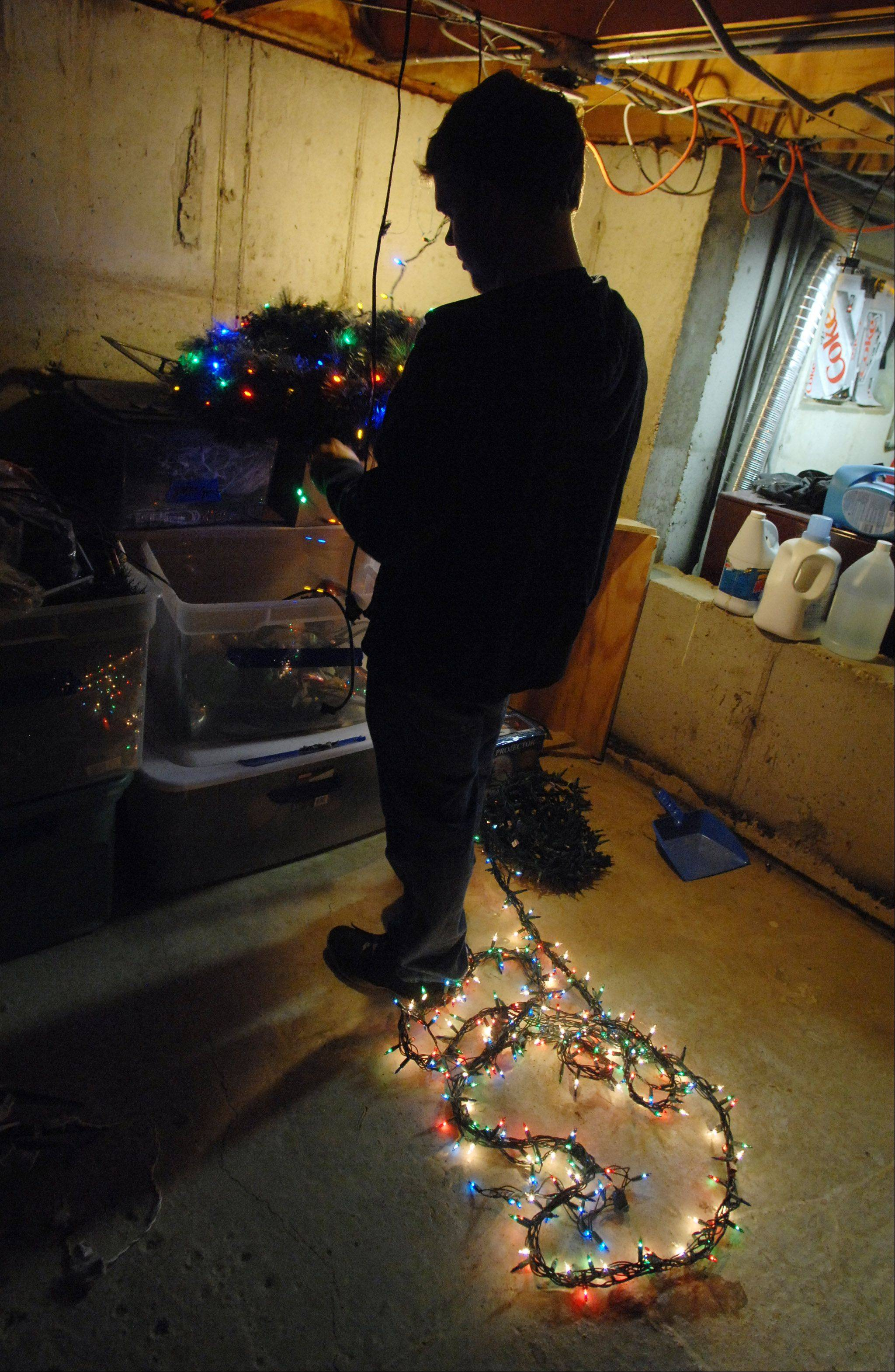 Gurnee resident Adam Germann tests out the lights before dragging them outside from his basement storage area.