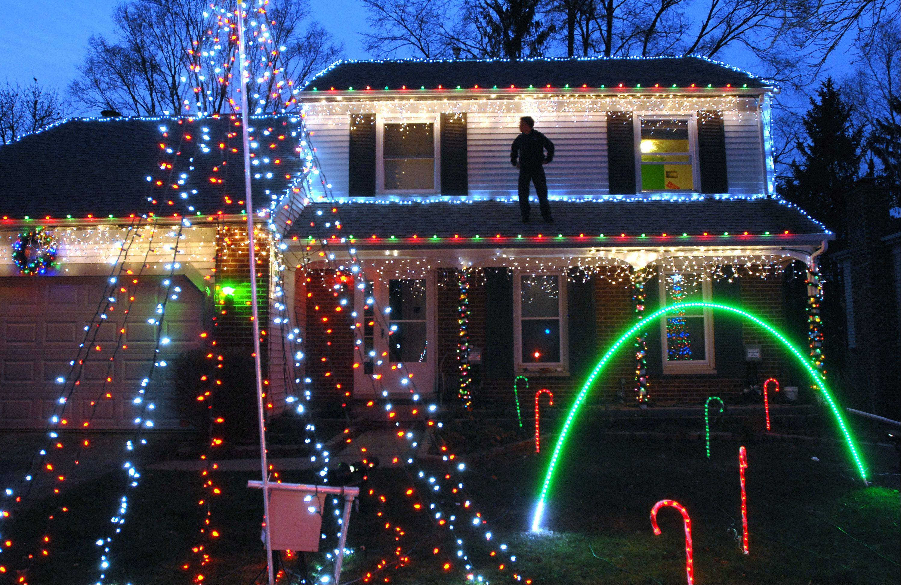 Germann makes a final inspection of his light show from the roof of his Prairie Oak Road residence before opening night on Thursday, Dec. 1. Germann takes food and money collections for the Northern Illinois Food Bank.