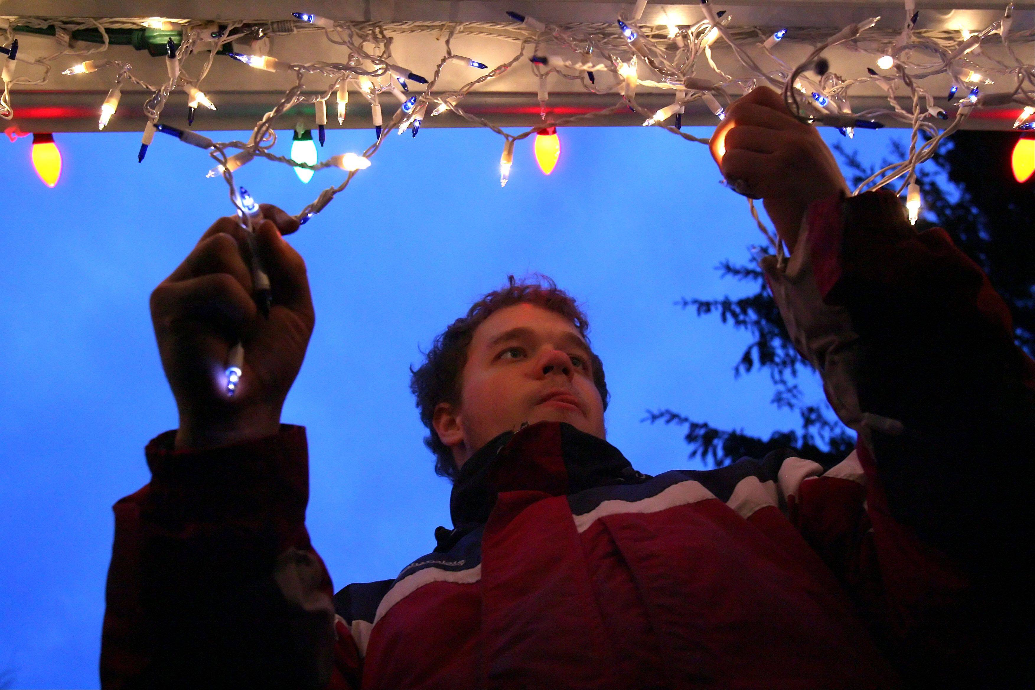 Germann makes adjustments to the Christmas lights on his front porch.