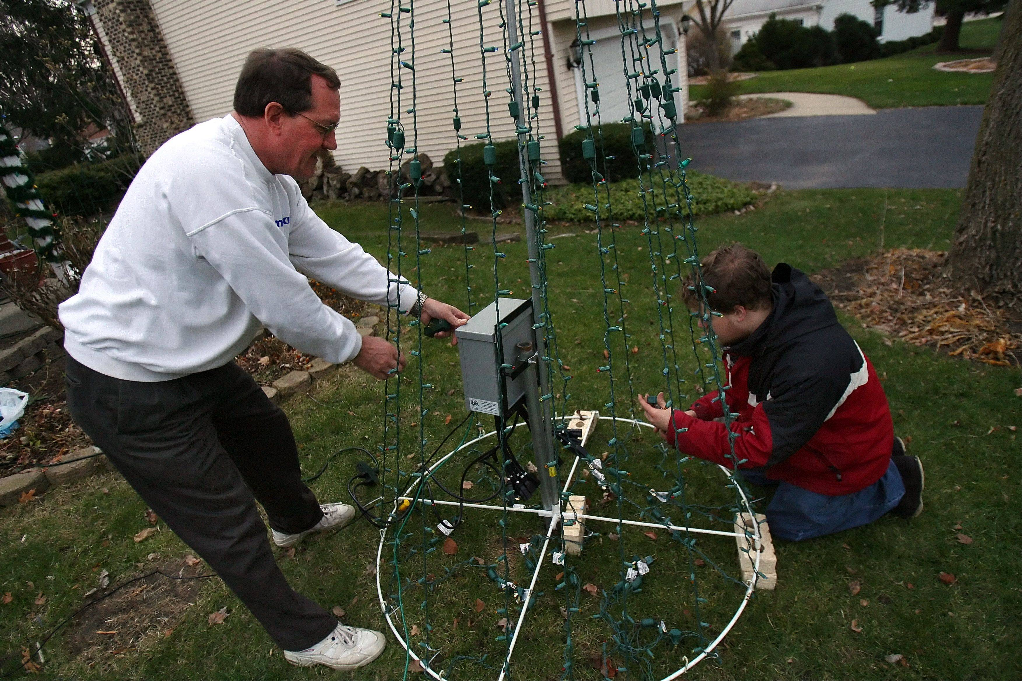 German and his father Arnold makes adjustments to the Christmas lights in their front yard.
