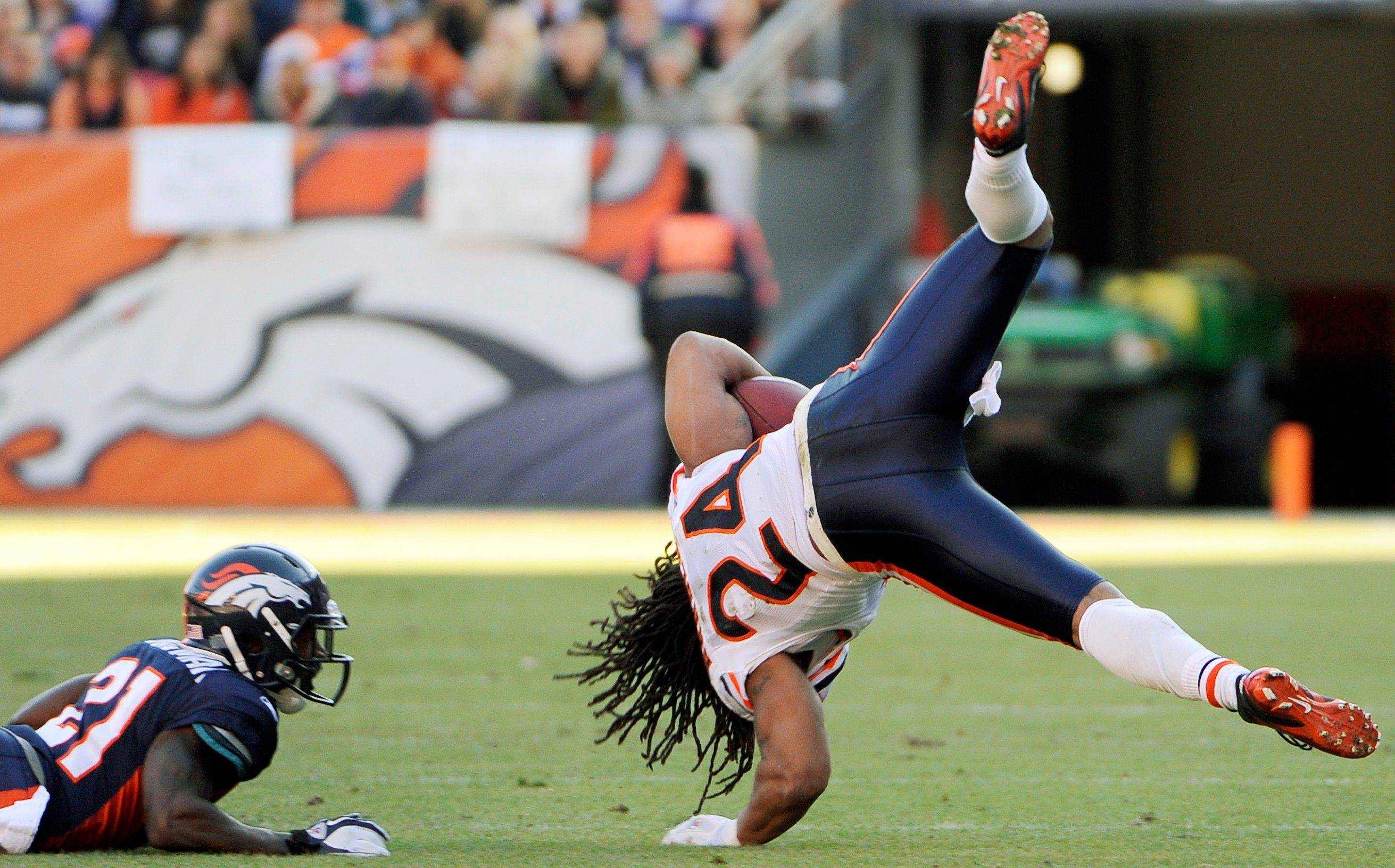Broncos cornerback Andre' Goodman trips up Bears running back Marion Barber int the first quarter Sunday in Denver.