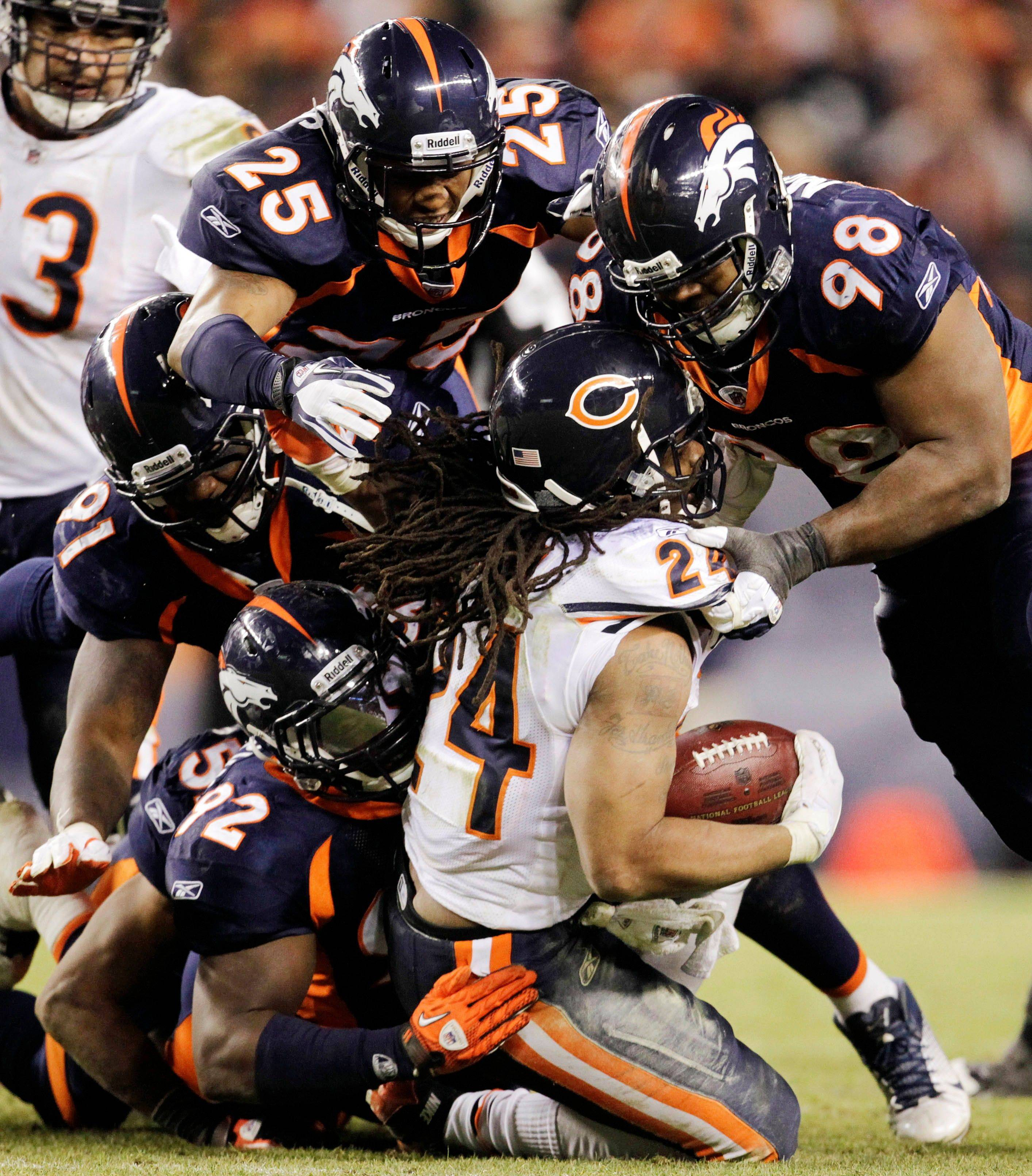 Chicago Bears running back Marion Barber (24) is tackled by the Denver Broncos defense late in the fourth quarter of an NFL football game, Sunday, in Denver. Denver won 13-10 in overtime.