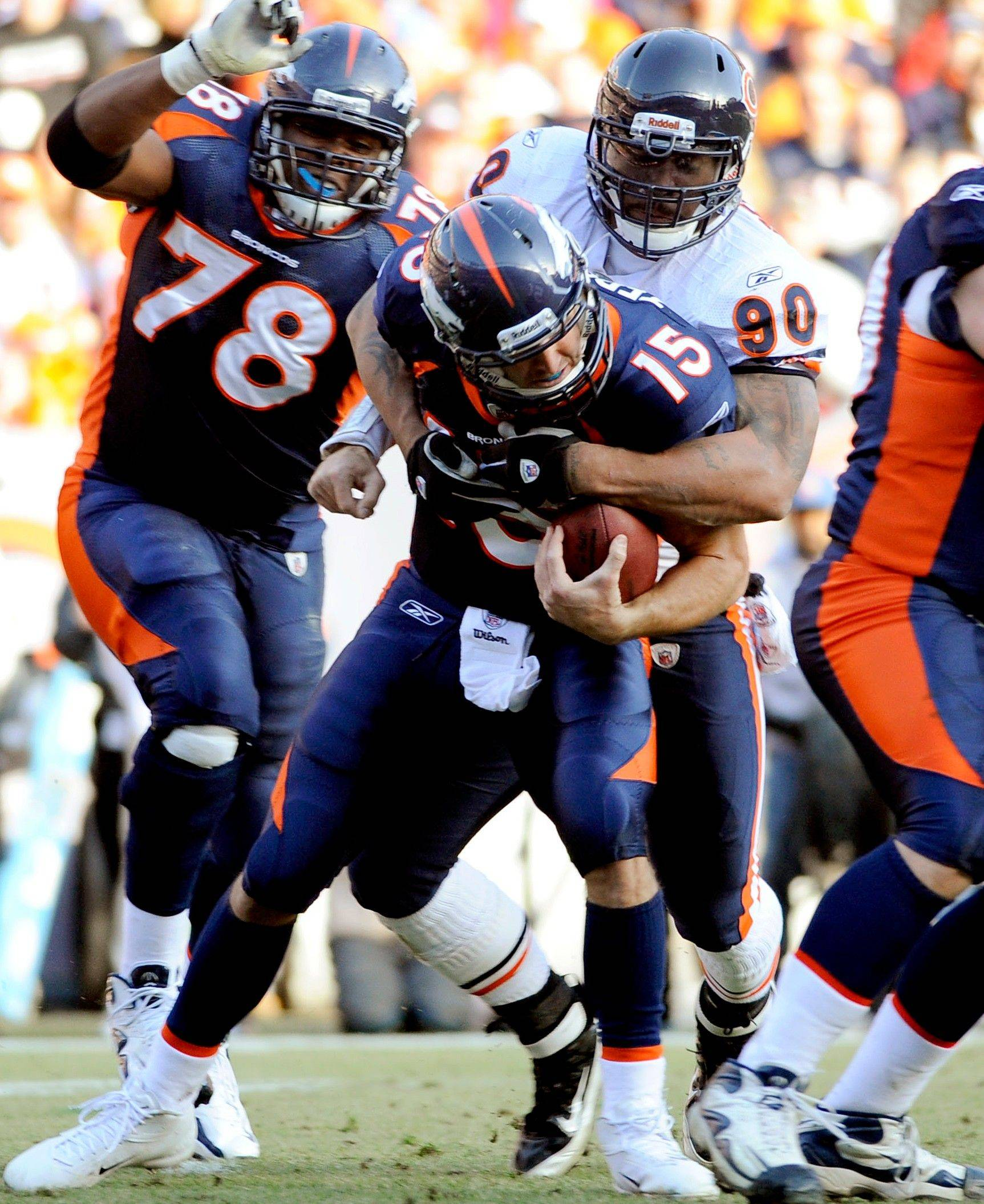 Denver Broncos quarterback Tim Tebow (15) is sacked by Chicago Bears defensive end Julius Peppers (90) during the second quarter.