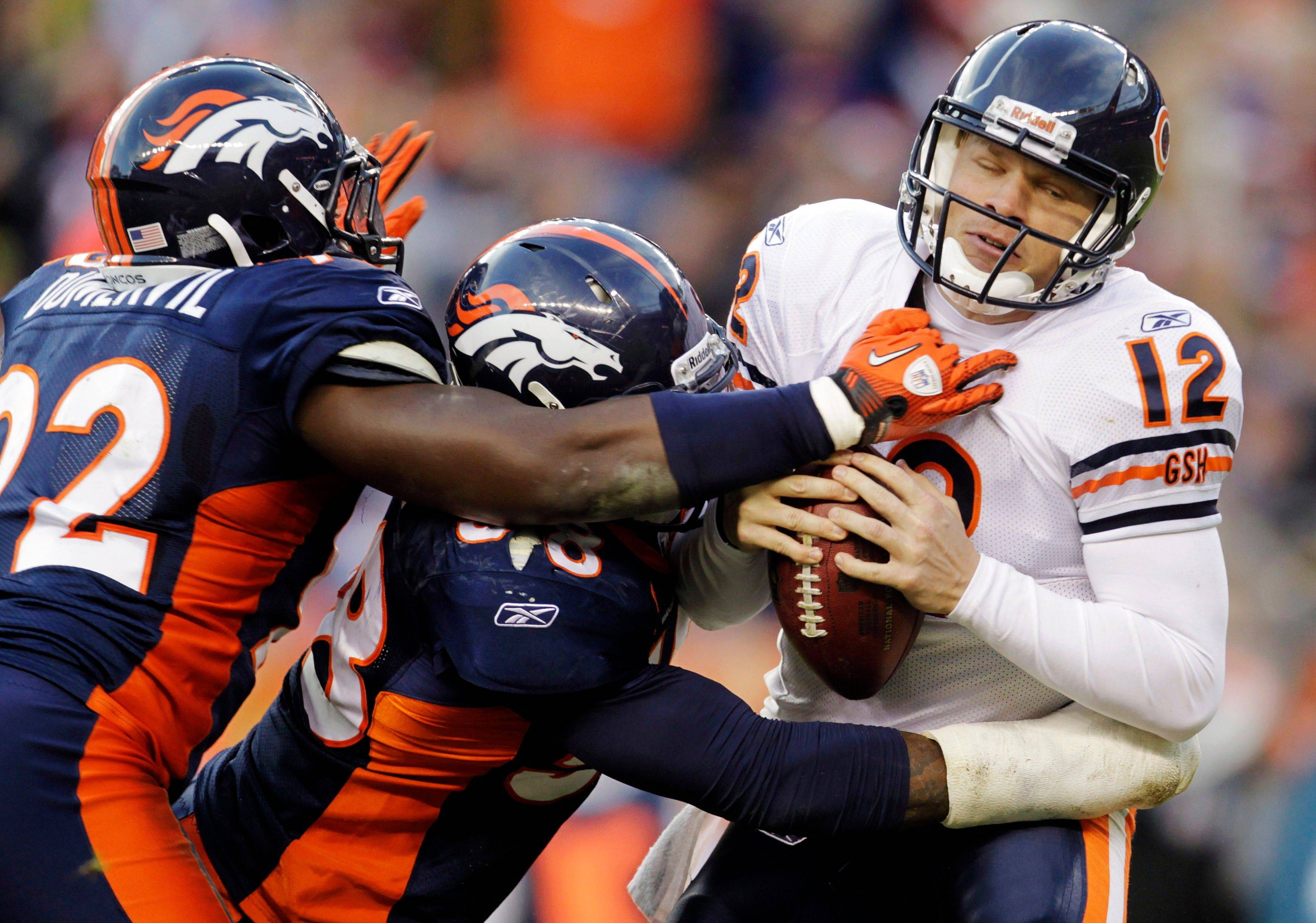 Chicago Bears quarterback Caleb Hanie (12) is sacked by Denver Broncos defensive end Elvis Dumervil (92) and outside linebacker Von Miller (58) in the third quarter.