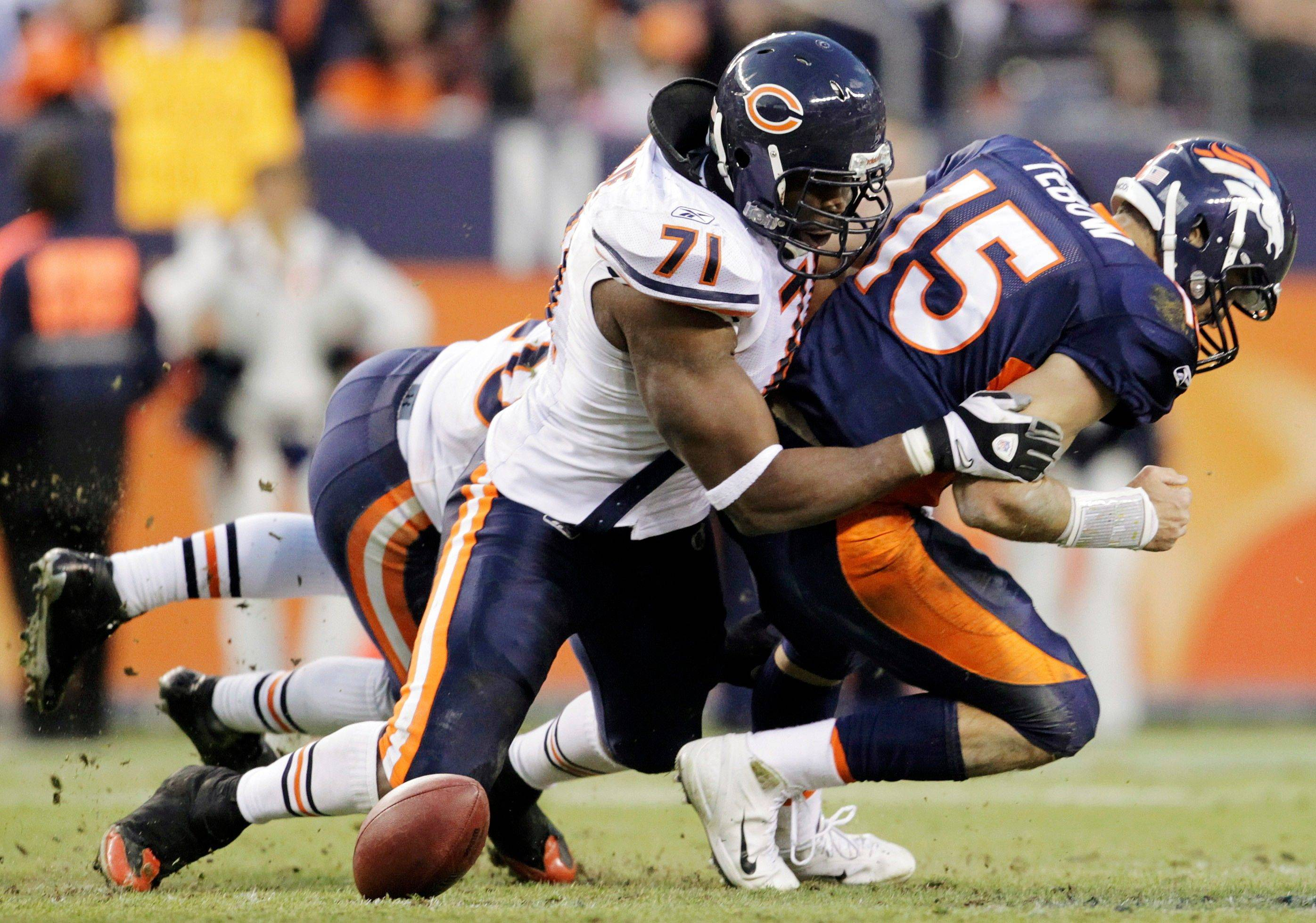 Chicago Bears defensive end Israel Idonije (71) hits Denver Broncos quarterback Tim Tebow (15) causing him to fumble the ball in the fourth quarter.