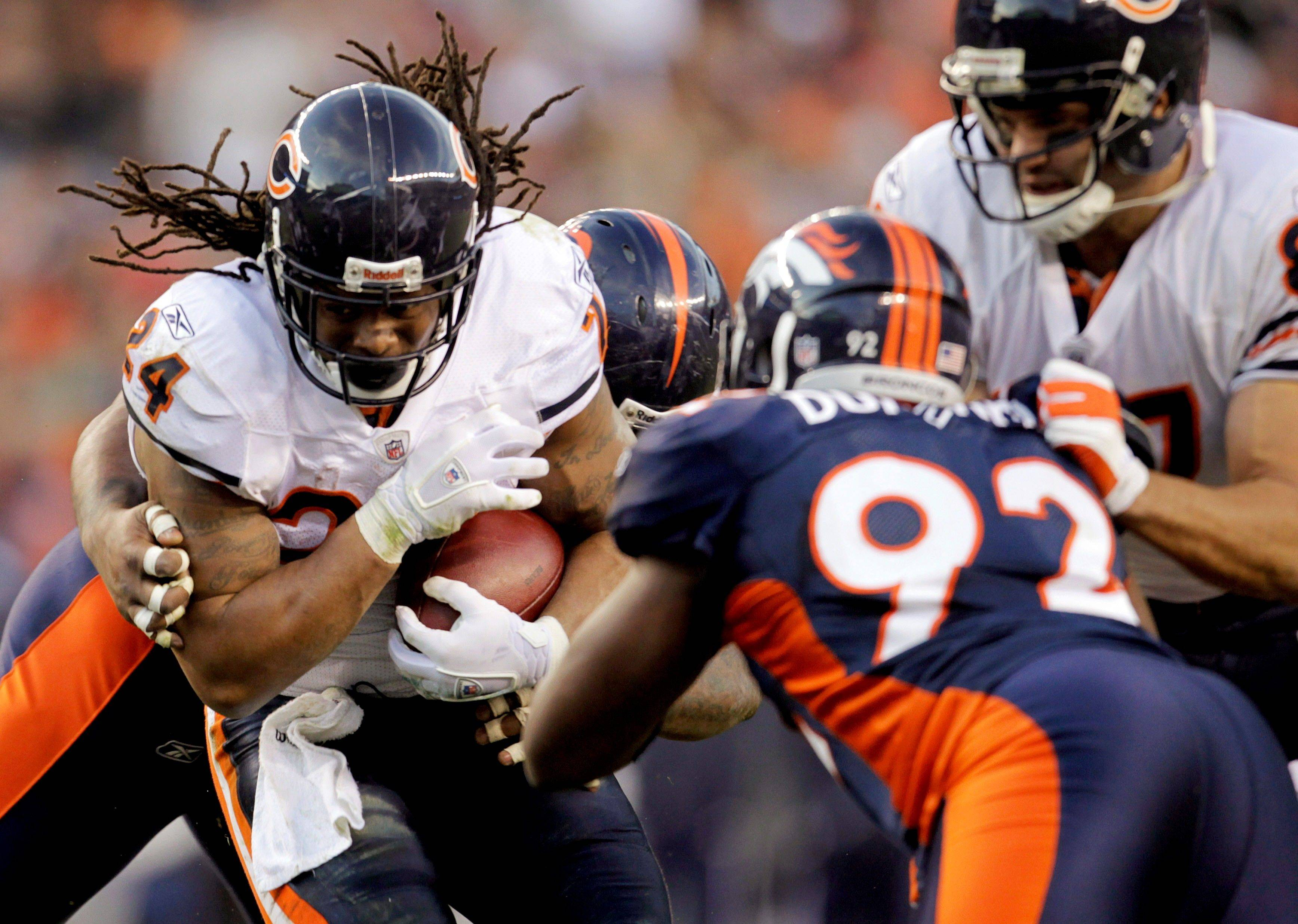 Chicago Bears running back Marion Barber (24) is hit by Denver Broncos defensive tackle Marcus Thomas, rear, and defensive end Elvis Dumervil (92) on his way to a first down in the third quarter.