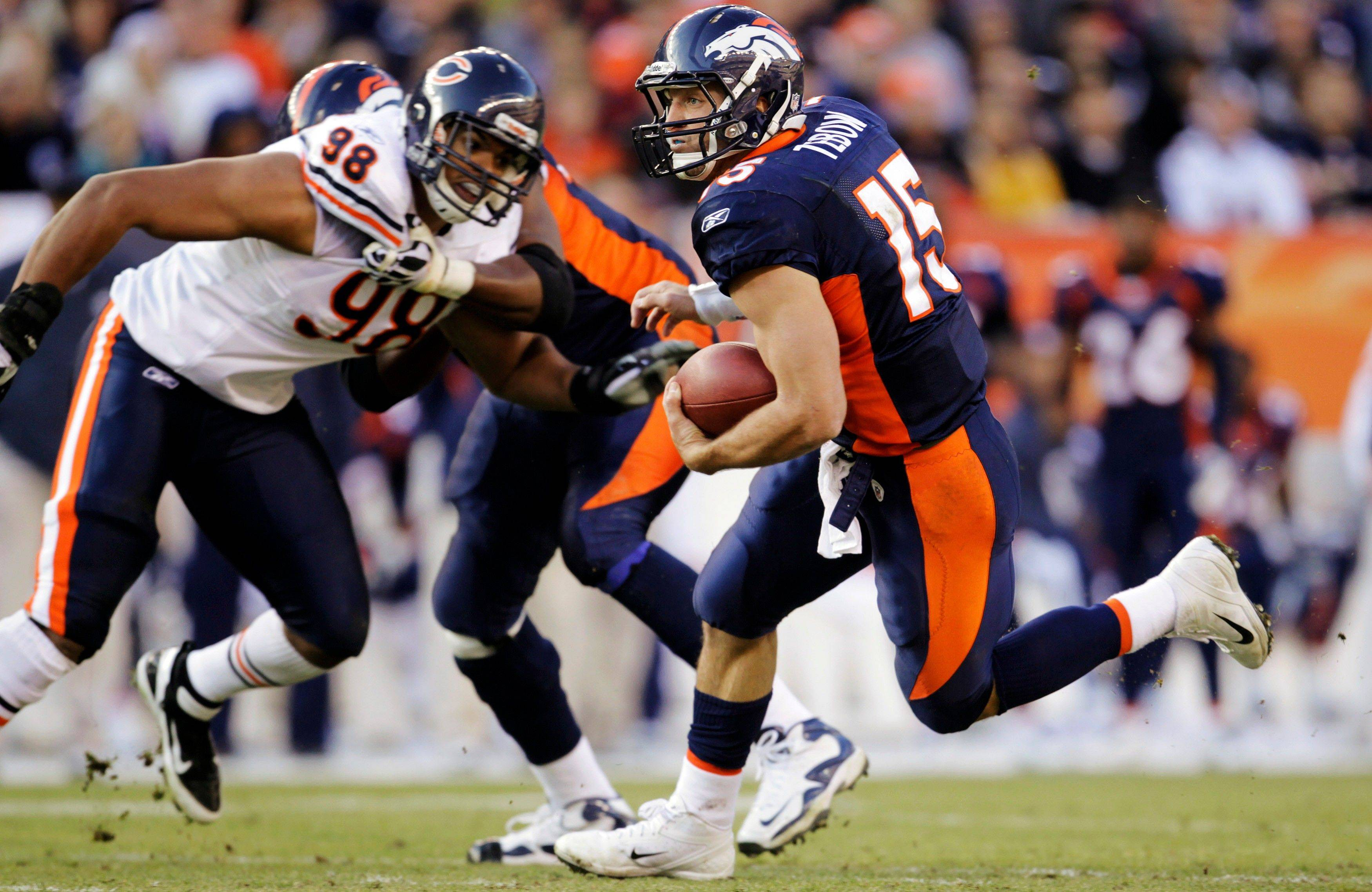 Denver Broncos quarterback Tim Tebow (15) runs for a first down as Chicago Bears defensive end Corey Wootton (98) is blocked in the second quarter.