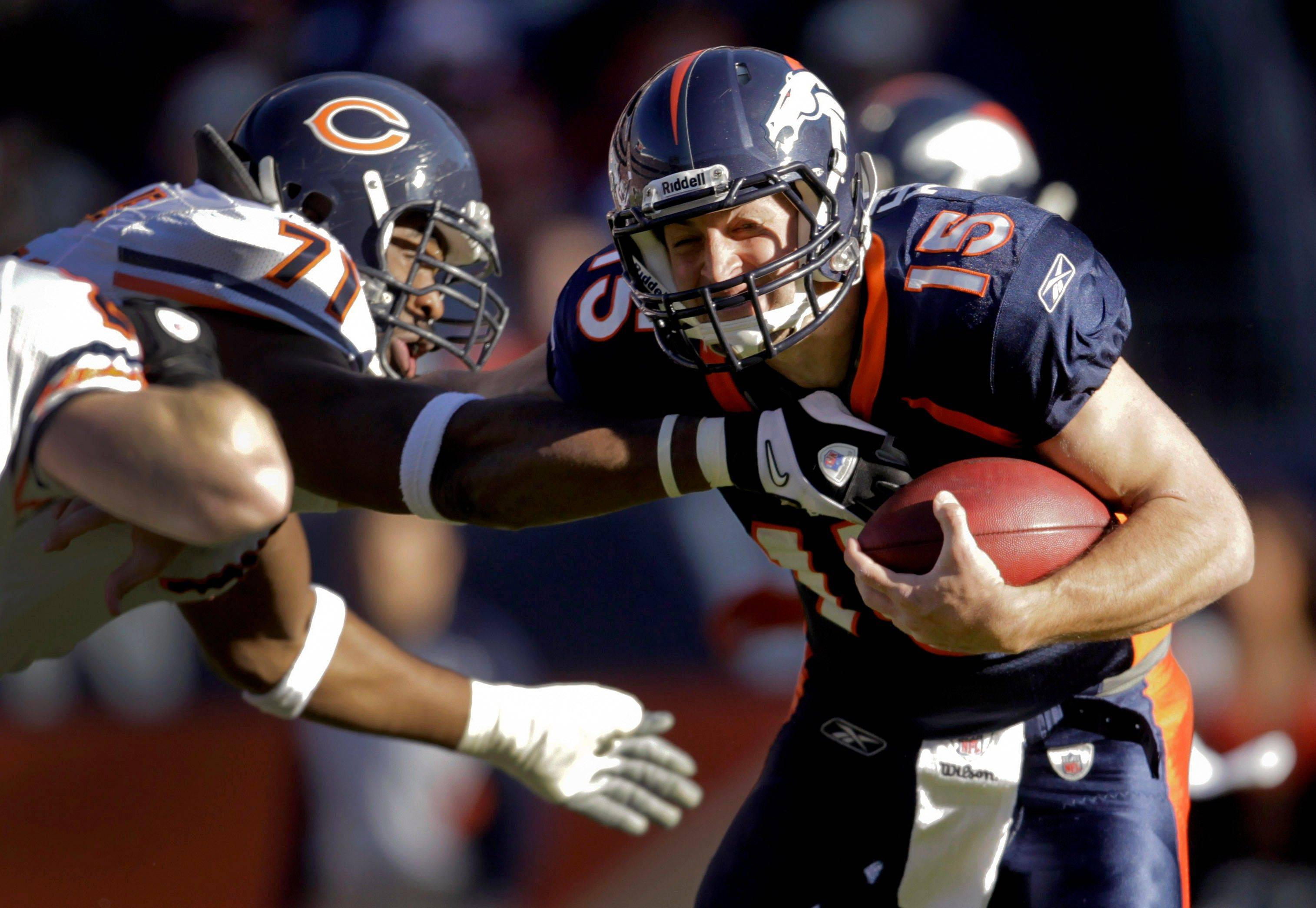 Denver Broncos quarterback Tim Tebow (15) stiff-arms Chicago Bears defensive end Israel Idonije (71) in the first quarter,