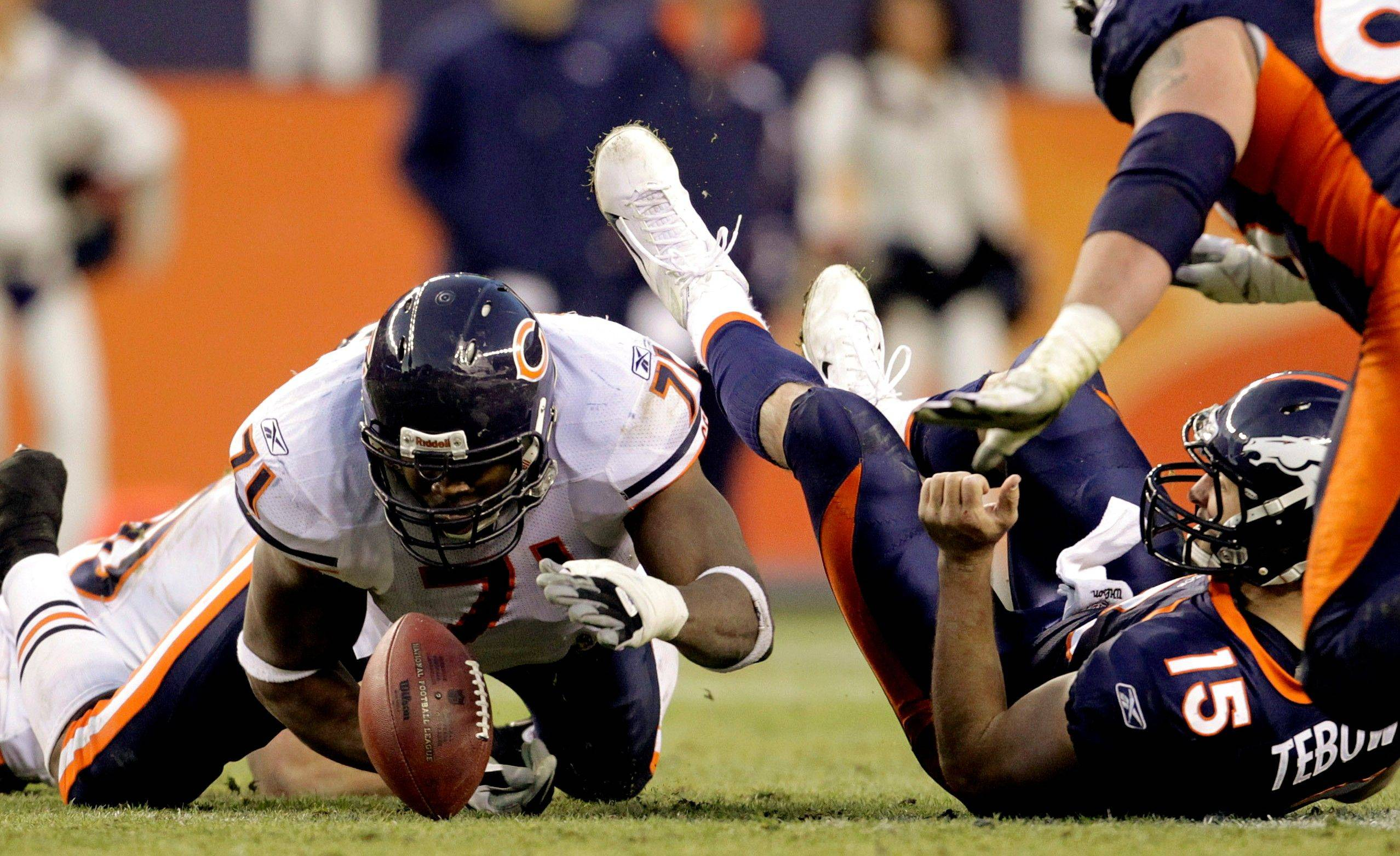 Chicago Bears defensive end Israel Idonije (71) hits Denver Broncos quarterback Tim Tebow (15), causing him to fumble the ball in the fourth quarter. Idonije recovered the fumble on the play.