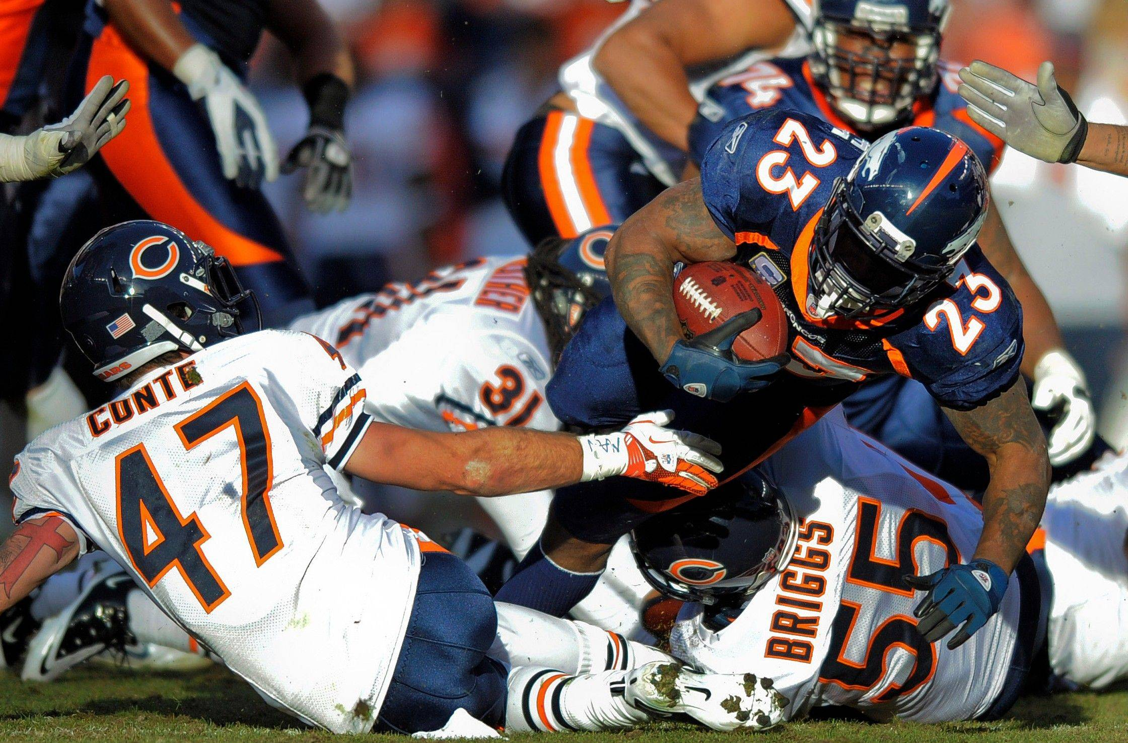 Denver Broncos running back Willis McGahee (23) is tripped up by Chicago Bears free safety Chris Conte (47) and outside linebacker Lance Briggs (55) in the second quarter.