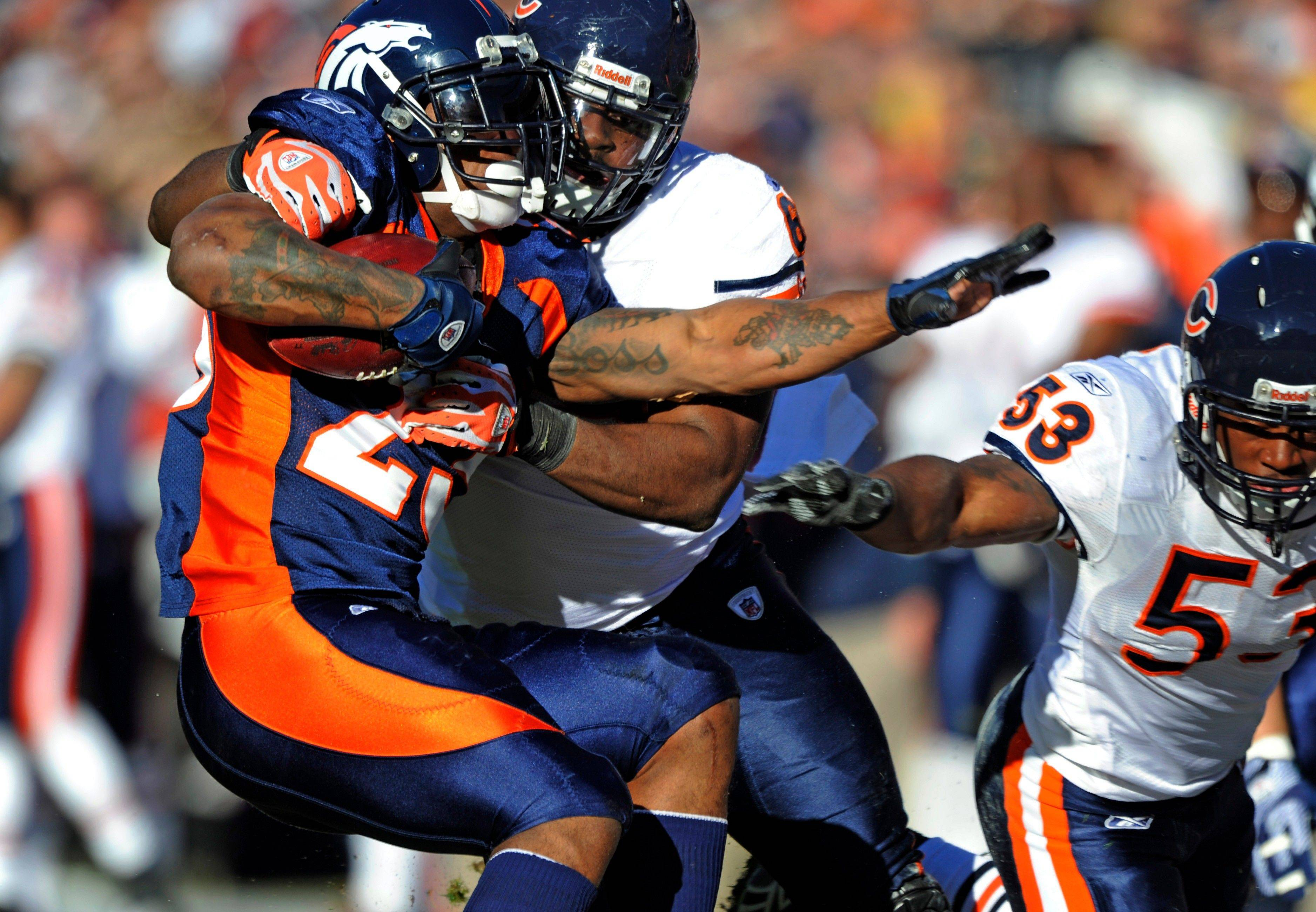 Denver Broncos running back Willis McGahee, left, is pulled down by Chicago Bears' Henry Melton, rear, during the first quarter,