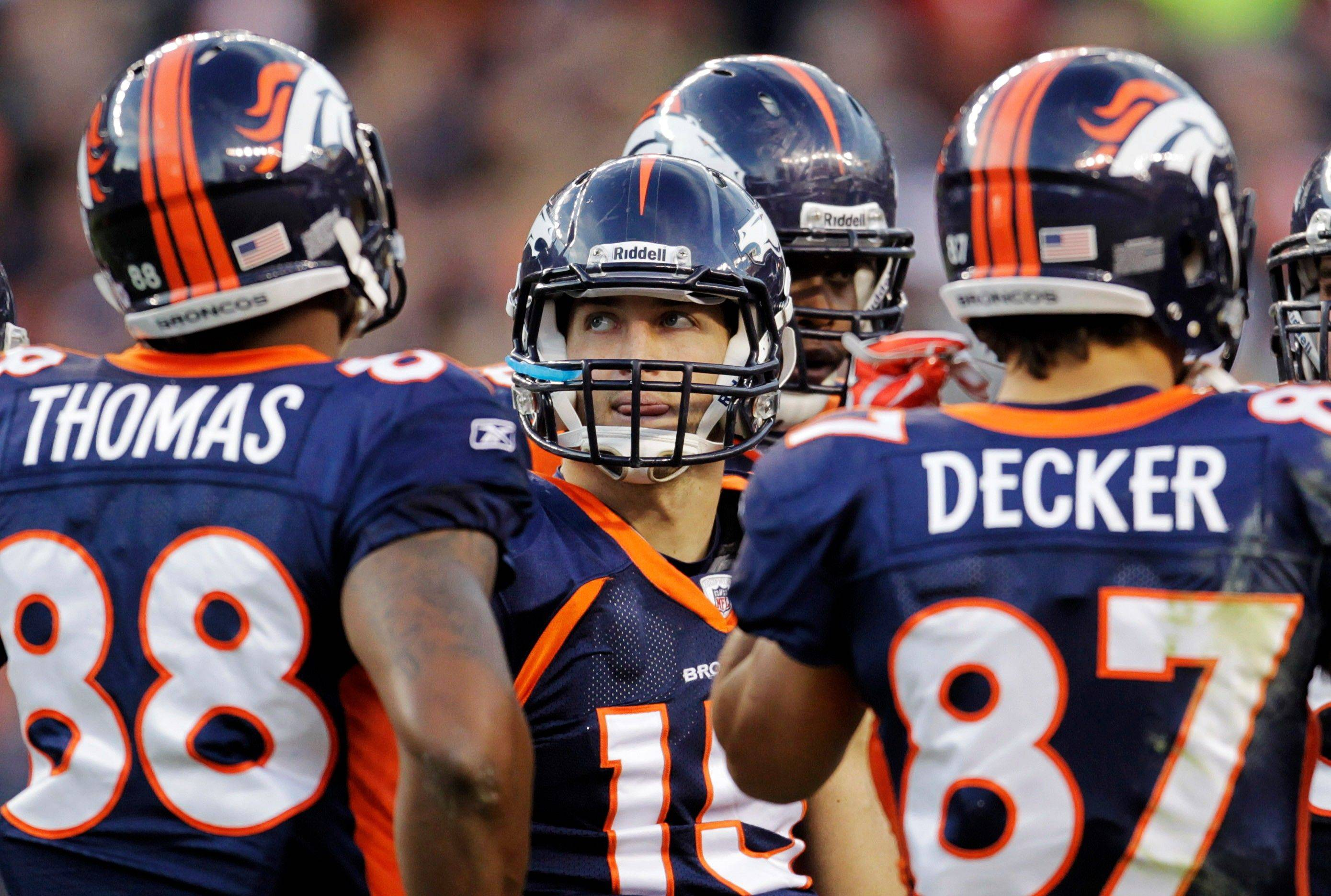 Denver Broncos quarterback Tim Tebow (15) stands in the huddle with wide receiver Demaryius Thomas (88) and wide receiver Eric Decker (87) after a touchdown by the Chicago Bears in the third quarter.