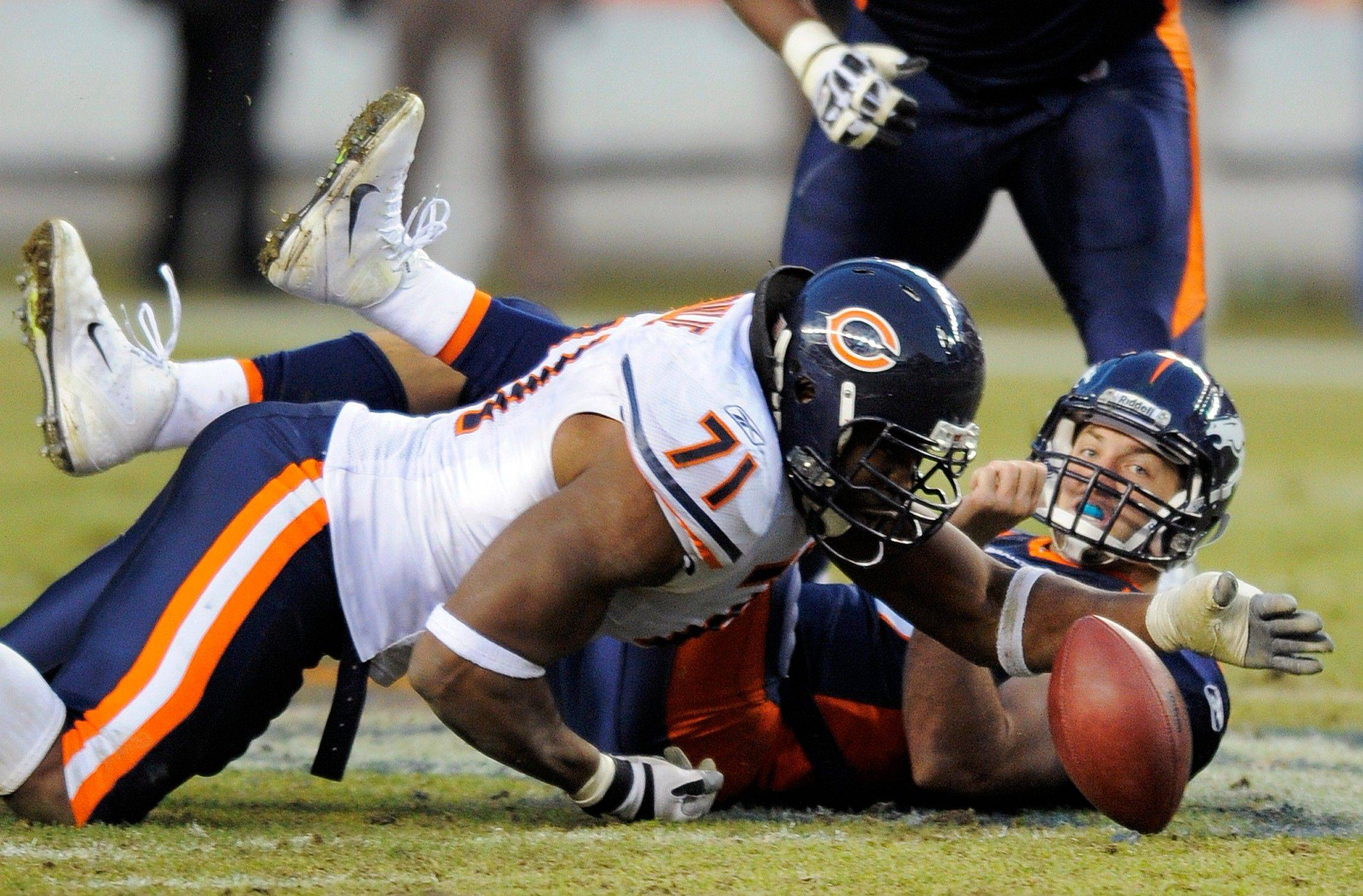 Chicago Bears defensive end Israel Idonije (71) recovers a fumble by Denver Broncos quarterback Tim Tebow (15) in the fourth quarter.