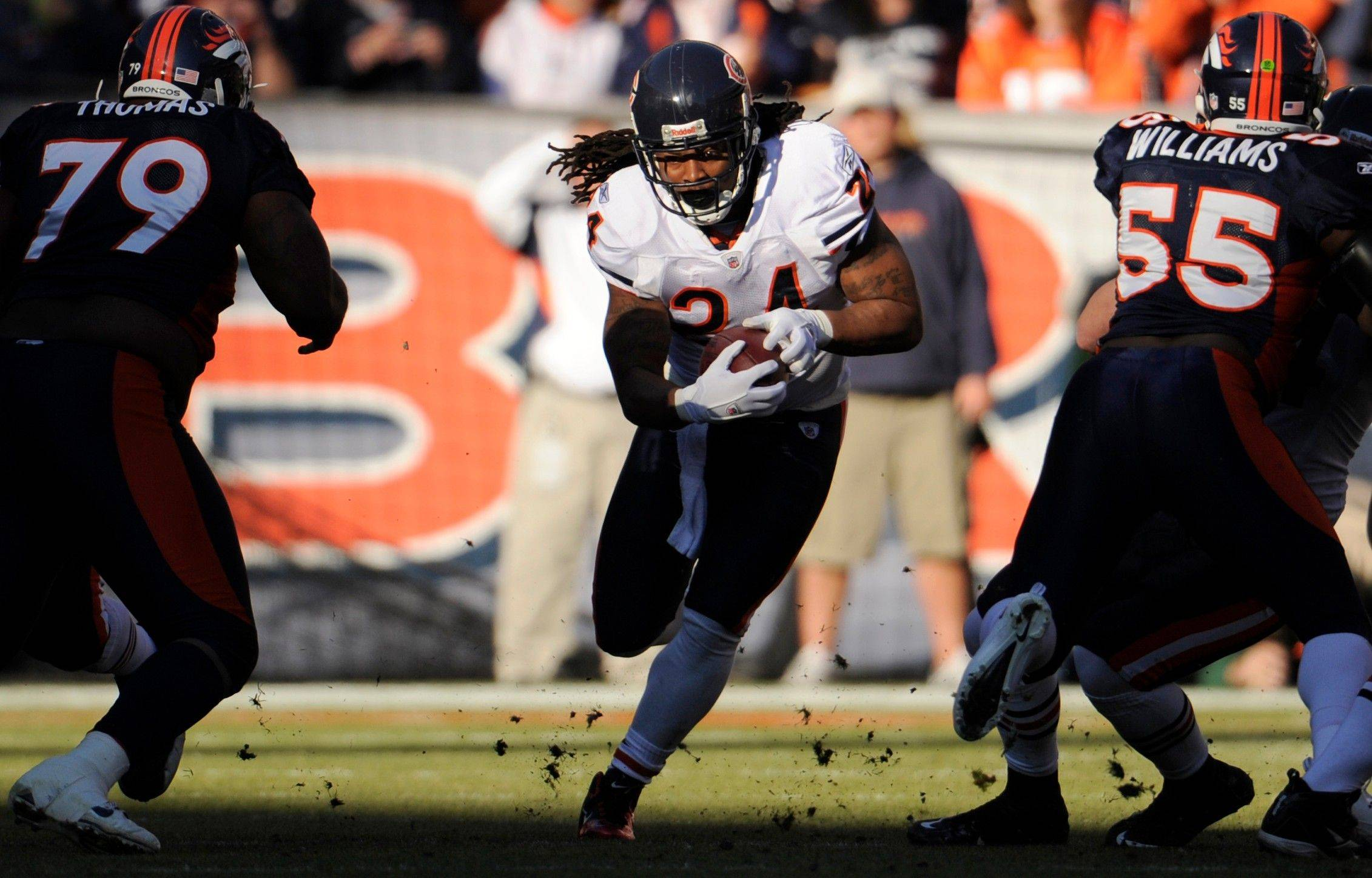 Chicago Bears running back Marion Barber rushes through a hole between Denver Broncos' Marcus Thomas (79) and D.J. Williams (55).