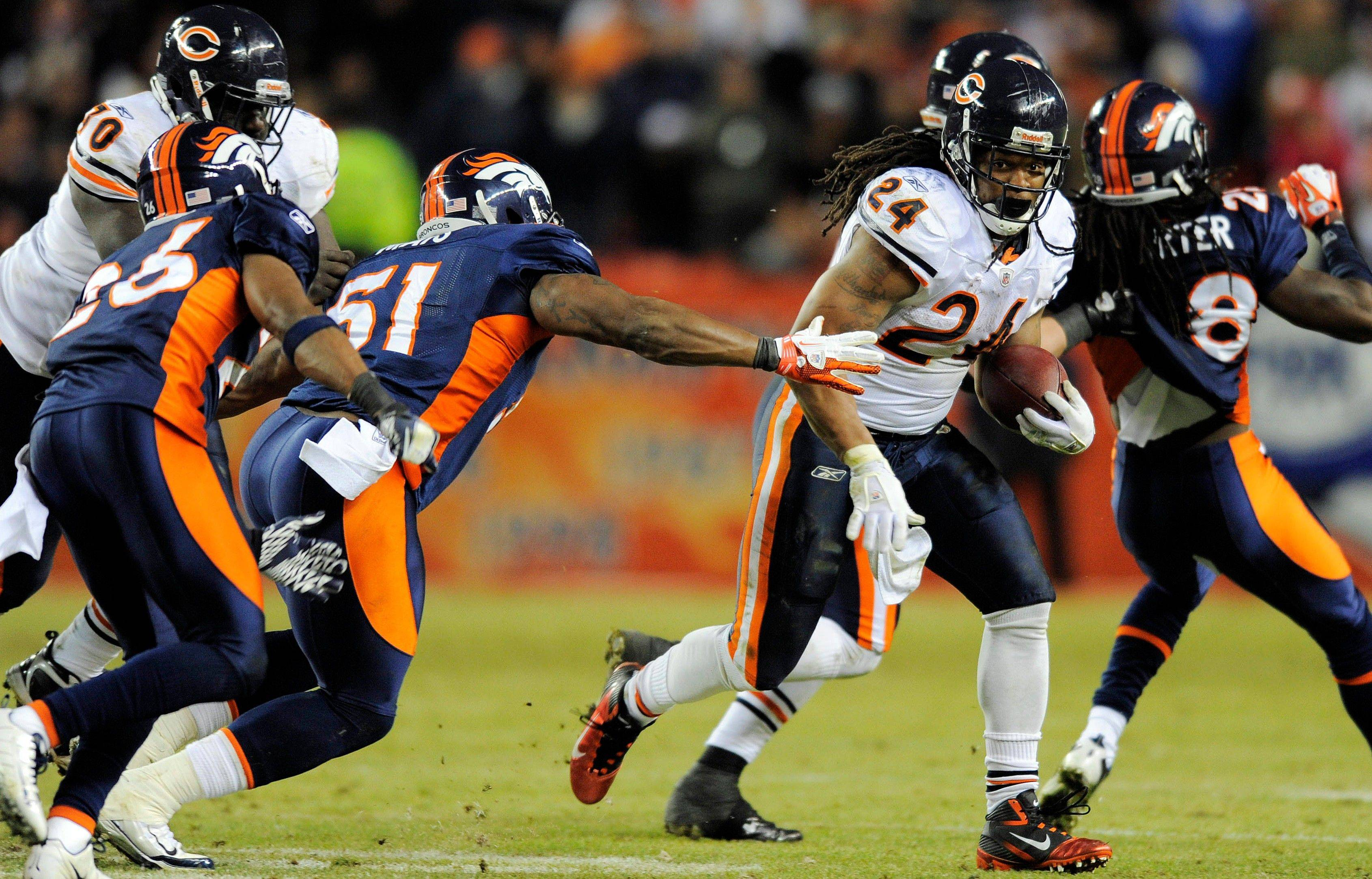 Chicago Bears running back Marion Barber (24) runs the ball against Denver Broncos middle linebacker Joe Mays (51) and free safety Rahim Moore (26) in the fourth quarter.