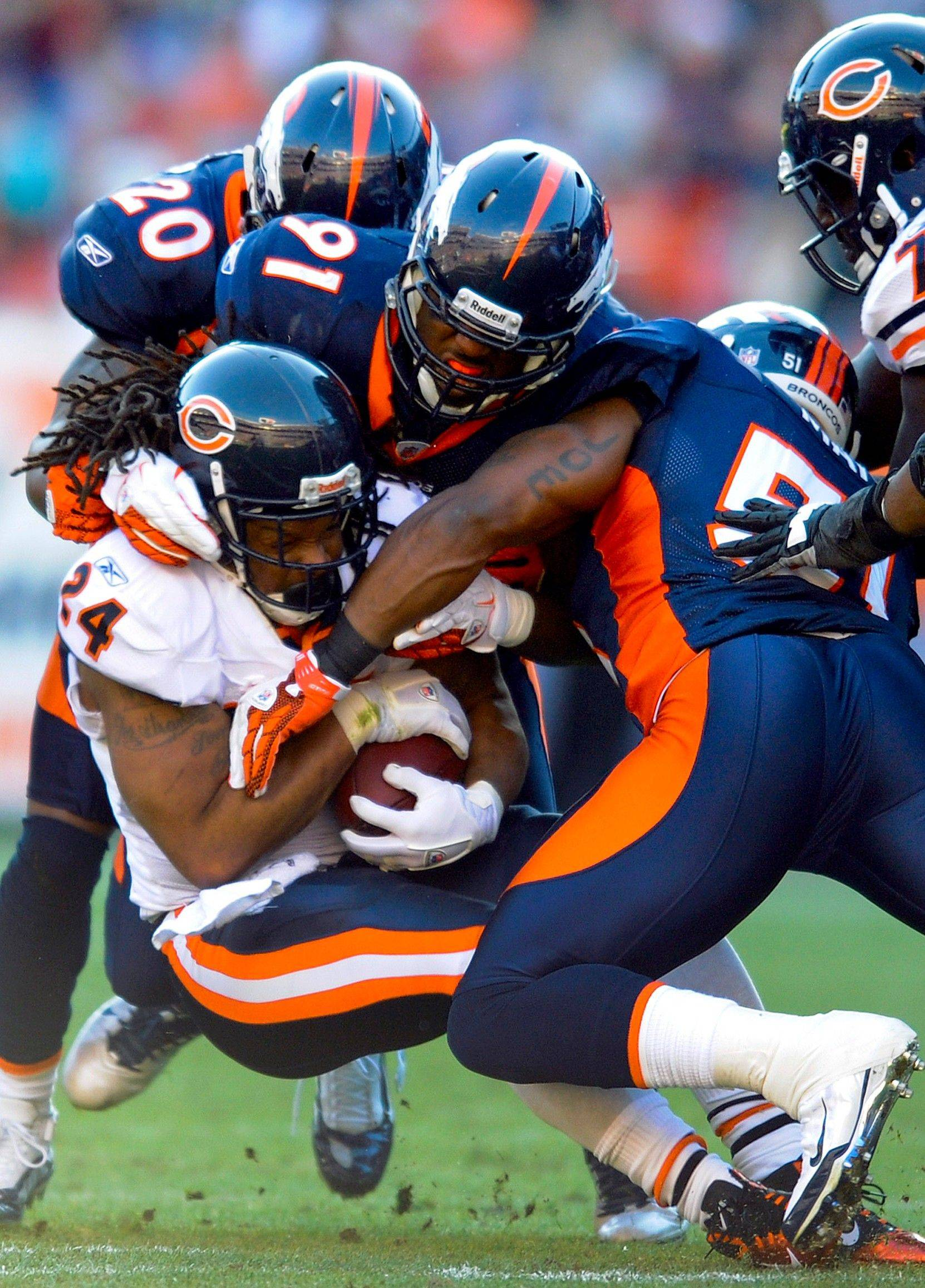 Chicago Bears running back Marion Barber (24) is tackled by Denver Broncos strong safety Brian Dawkins (20), defensive end Robert Ayers (91) and middle linebacker Joe Mays (51) in the first quarter.