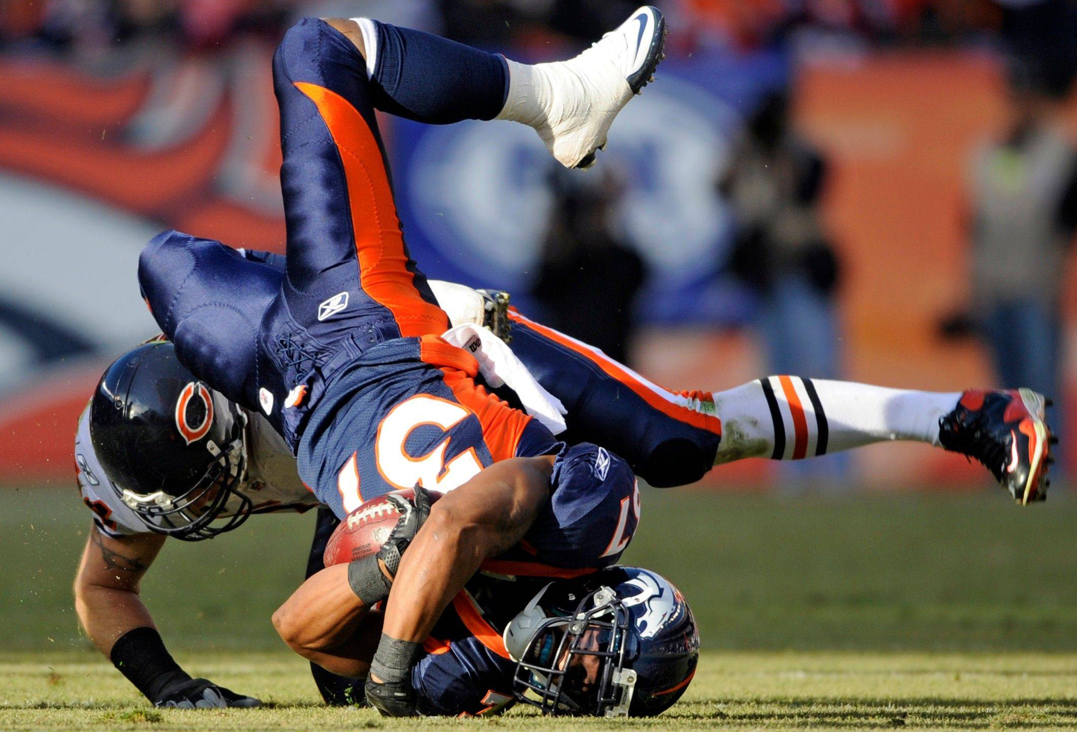 Denver Broncos running back Jeremiah Johnson (37) is upended by Chicago Bears' Brian Urlacher, left, during the second quarter.