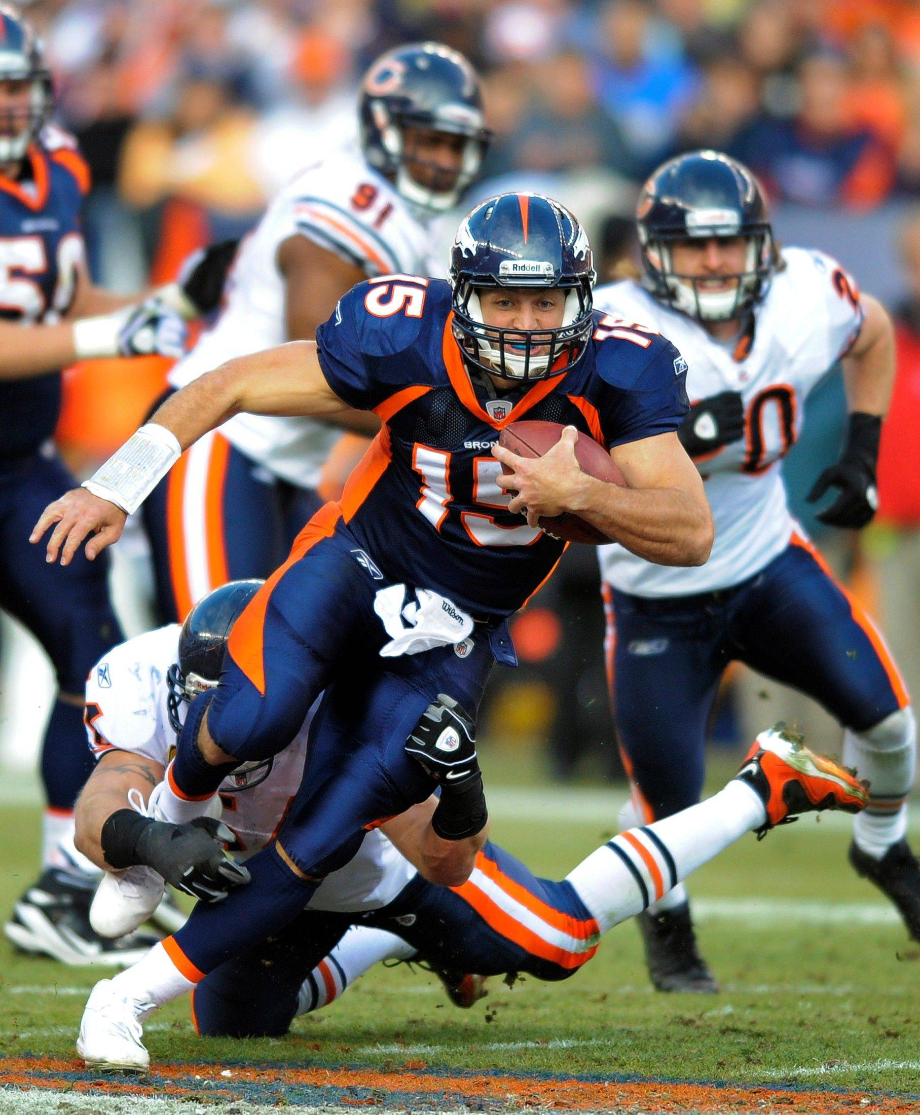 Denver Broncos quarterback Tim Tebow (15) is hit by Chicago Bears middle linebacker Brian Urlacher (54) as he runs for a first down in the second quarter.