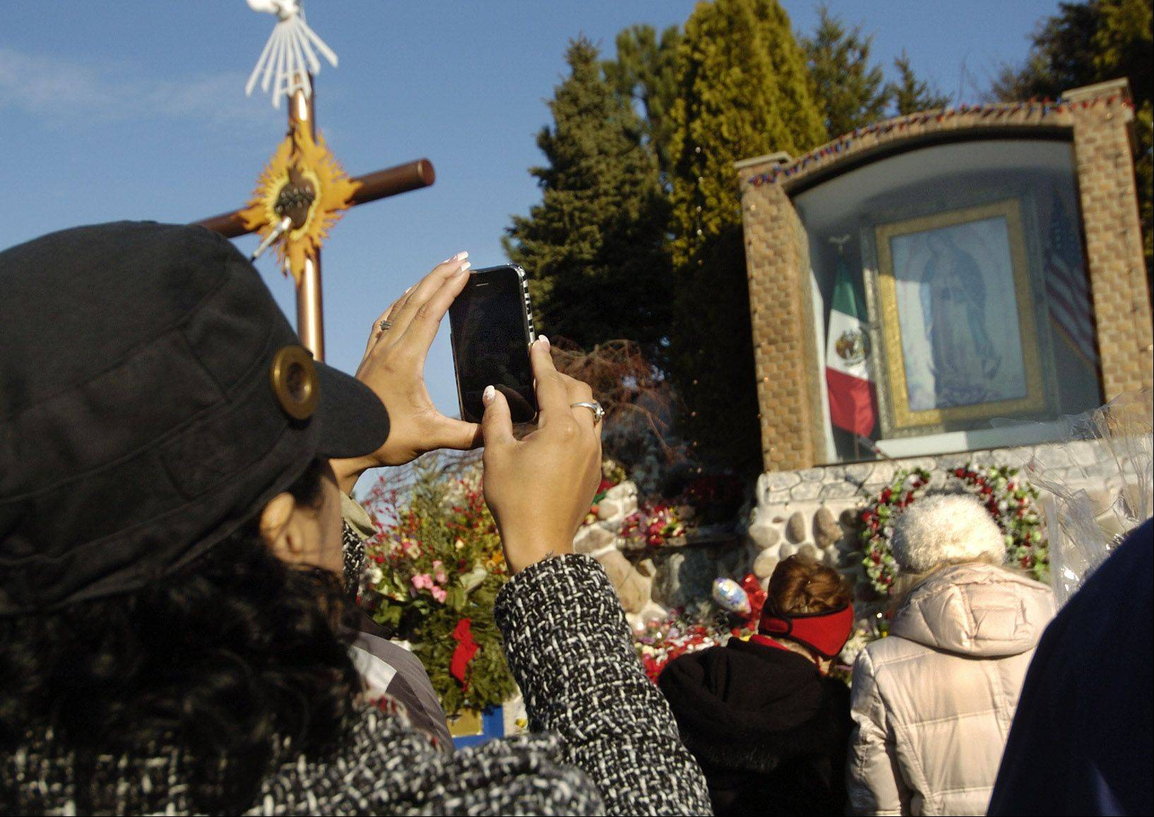 Maria Perez of Schaumburg takes a picture of the Shrine of Our Lady of Guadalupe in Des Plaines.