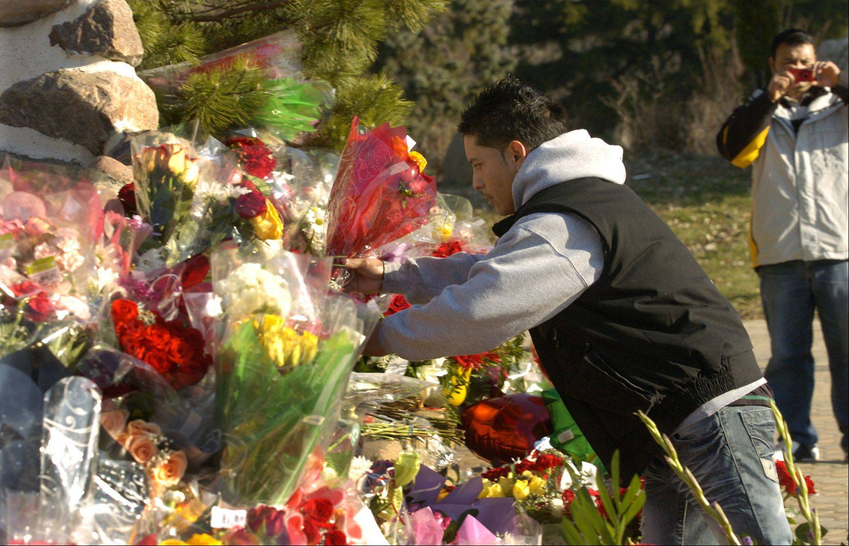 Jorge Cruz of Chicago places roses on the Shrine of Our Lady of Guadalupe in Des Plaines.