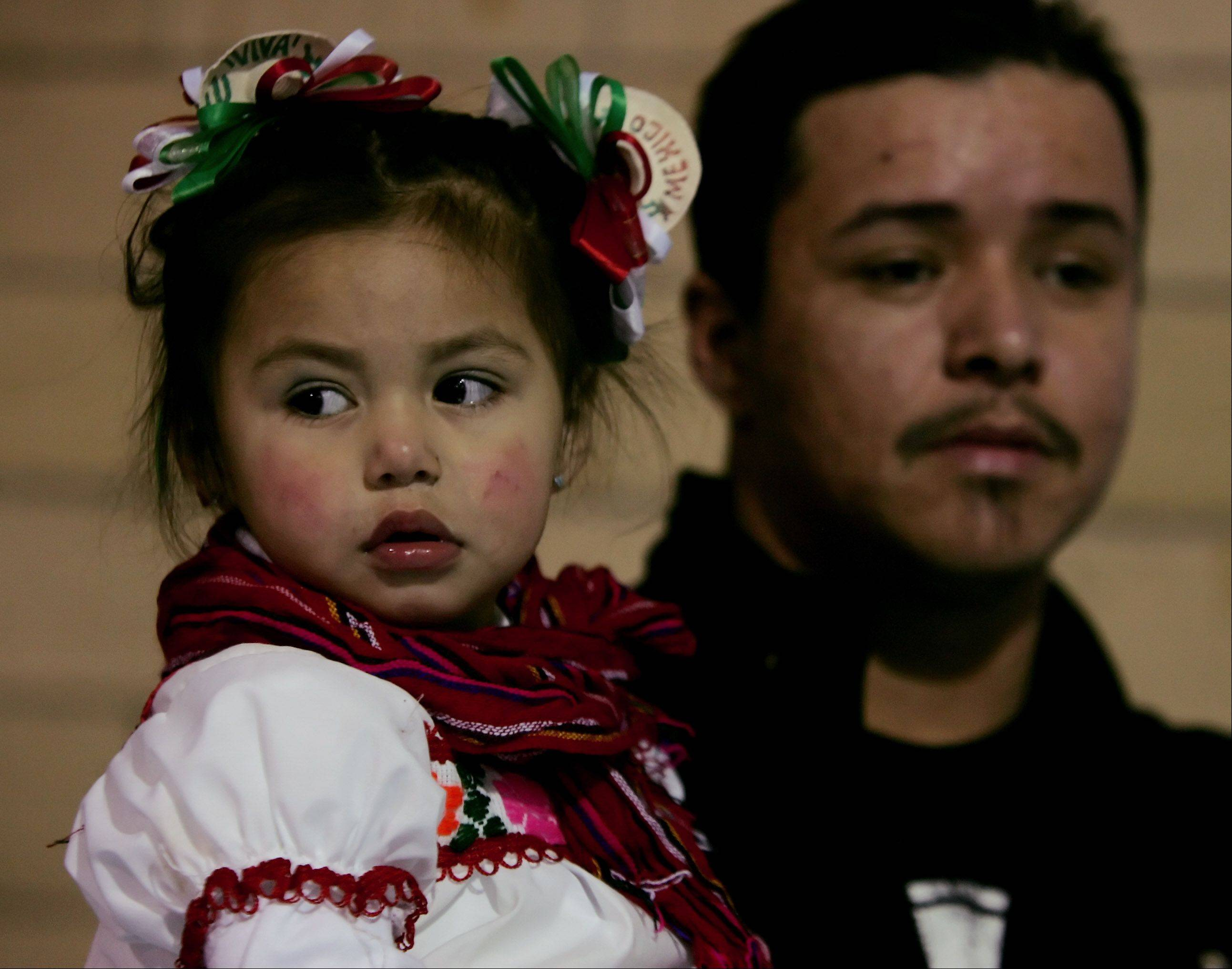 Angelina Diaz, 2, of Arlington Heights is held by her father, Javier, as they attend the Singing Rosary during the annual celebration honoring Our Lady of the Guadalupe Sunday at Maryville Academy in Des Plaines. Crowds in excess of 100,000 people are expected to attend the two day festival.
