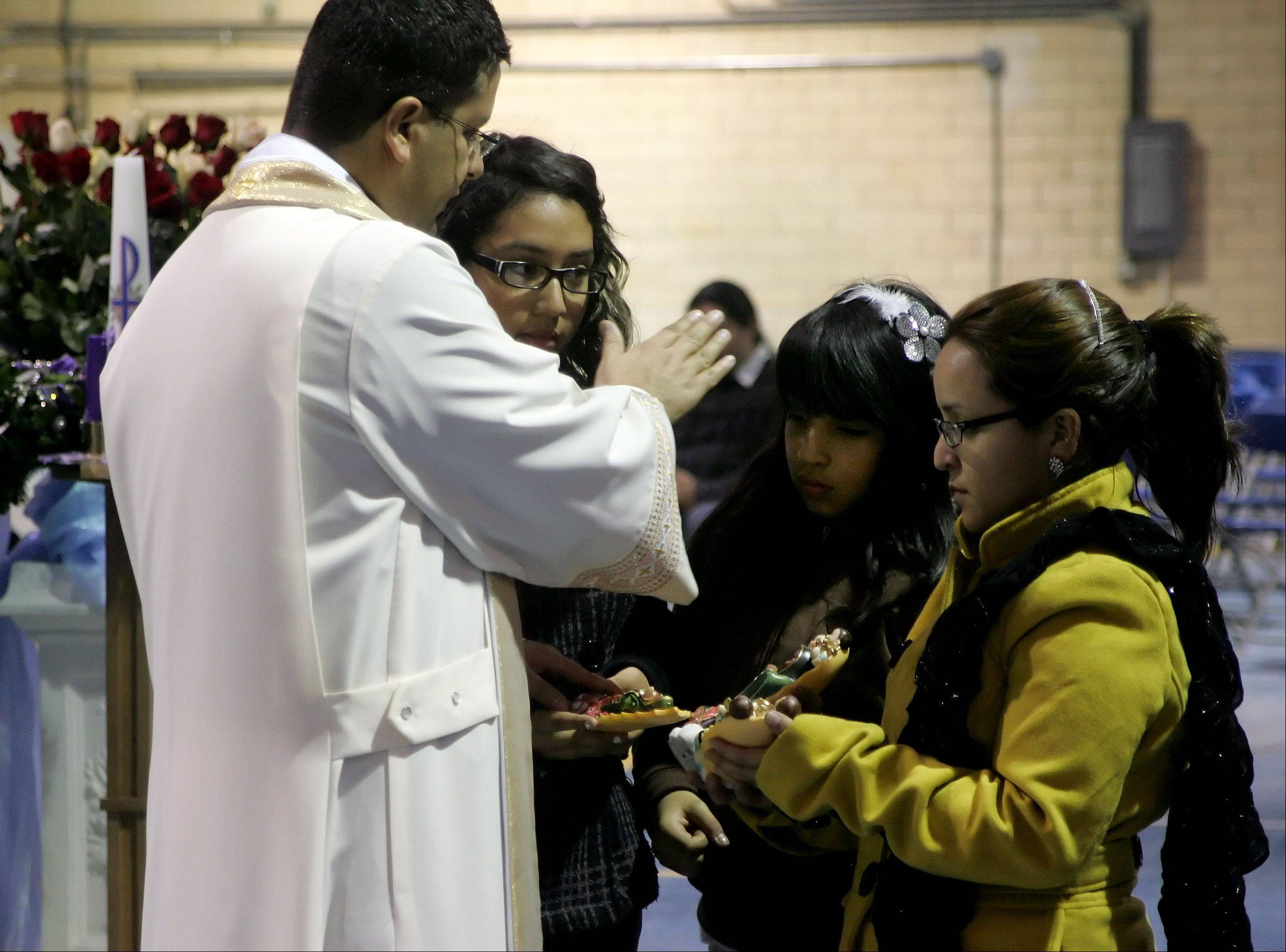 Father Miguel Martinez blesses Jennifer, Dulce, and Nancy Palomar of Elgin during the annual celebration honoring Our Lady of the Guadalupe Sunday at Maryville Academy in Des Plaines. Crowds in excess of 100,000 people are expected to attend the two day festival.
