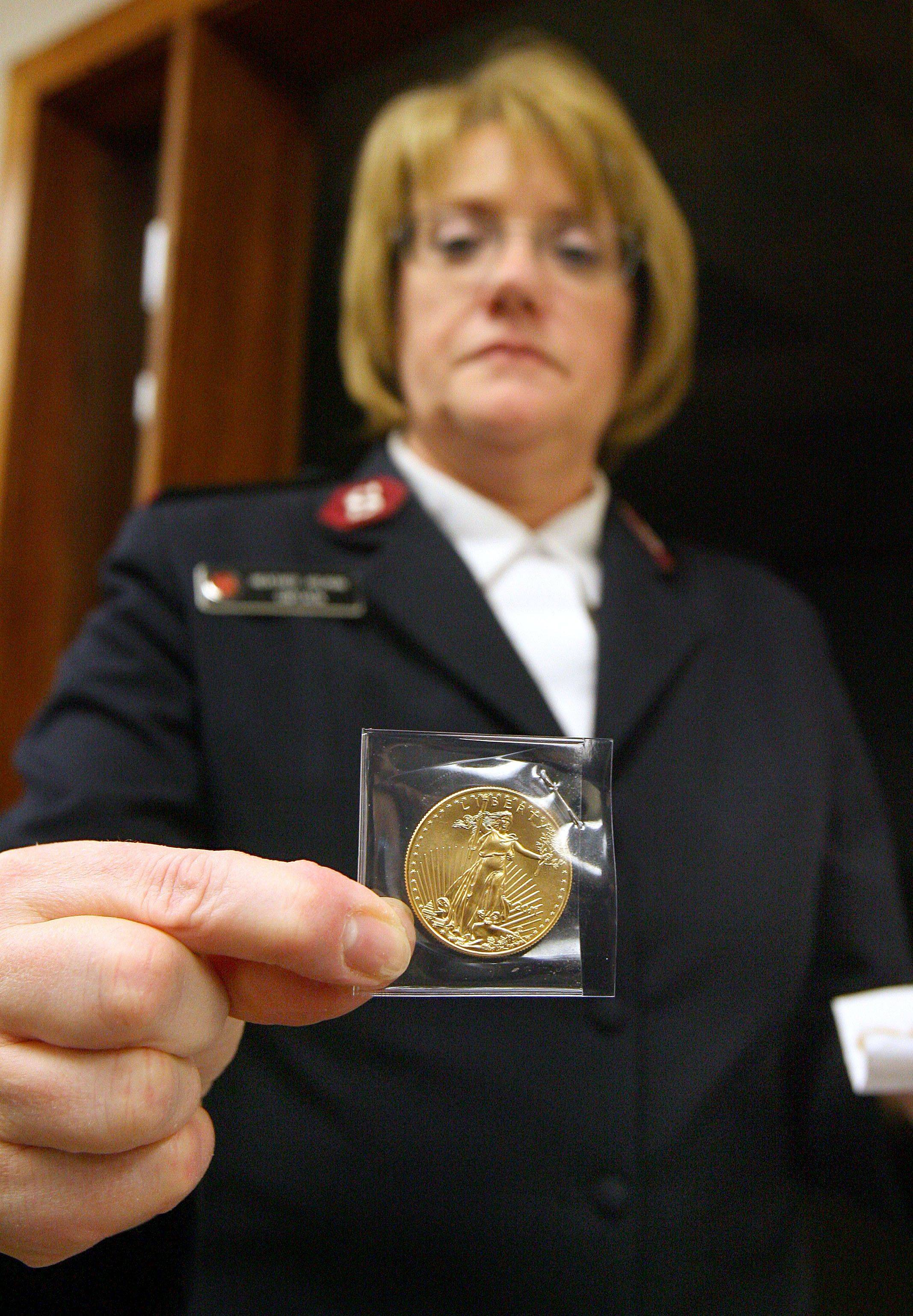 Salvation Army Waukegan Corps Capt. Heather Holman holds one of the 17 gold coins found in various Lake County kettles this winter. The coins have an estimated value of around $7,000.