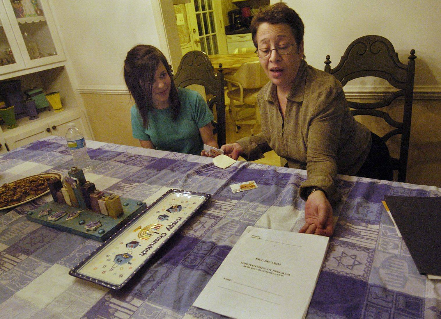 Mariah Reeves with her mom, Sandy, of Hanover Park, looks over the list of 13 service projects she needs to complete before her bat mitzvah. Mariah Reeves has decided to help the Saavedra family to satisfy one of the 13 good deeds. The Saavedras live in Carpentersville and have fallen on hard times.