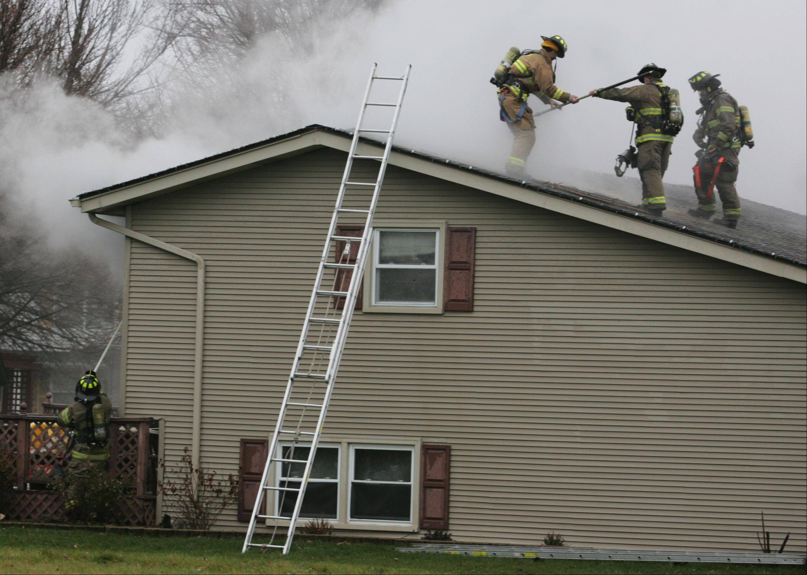 Firefighters cut a hole in the roof of a home on Sheffield Drive in Elgin where a Christmas tree caught fire Wednesday. All of the residents escaped safely, and several dogs were rescued as well.