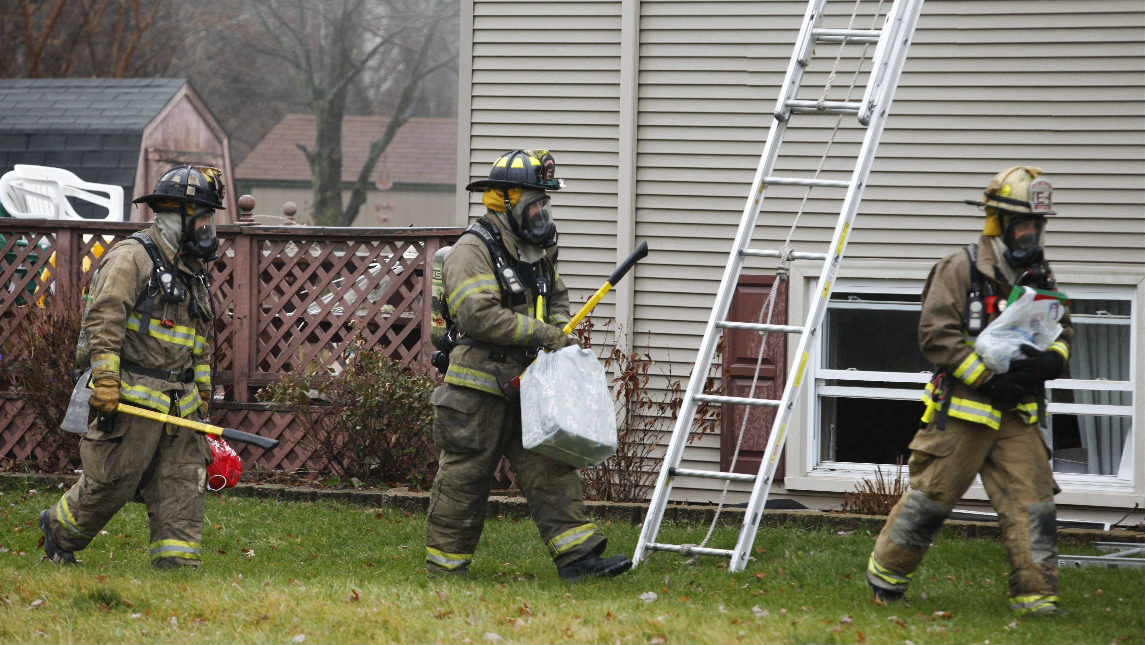 Elgin firefighters carry gift packages which they were able to salvage from the home after a Christmas tree caught fire.