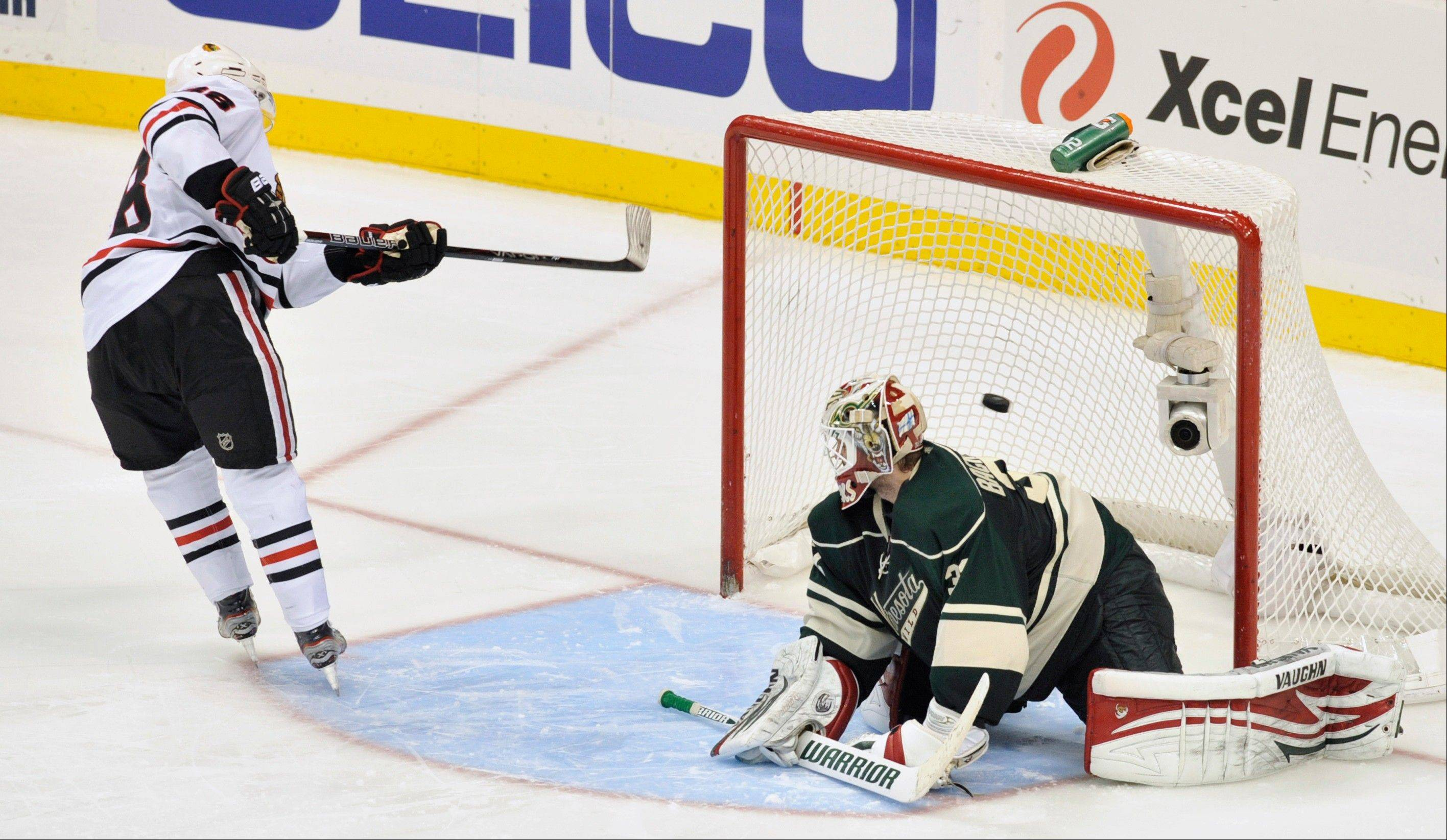 The Blackhawks' Patrick Kane puts the game-winning shootout goal past Wild goalie Niklas Backstrom on Wednesday night. Kane deked and slowed down long enough to get an open net on Backstrom.