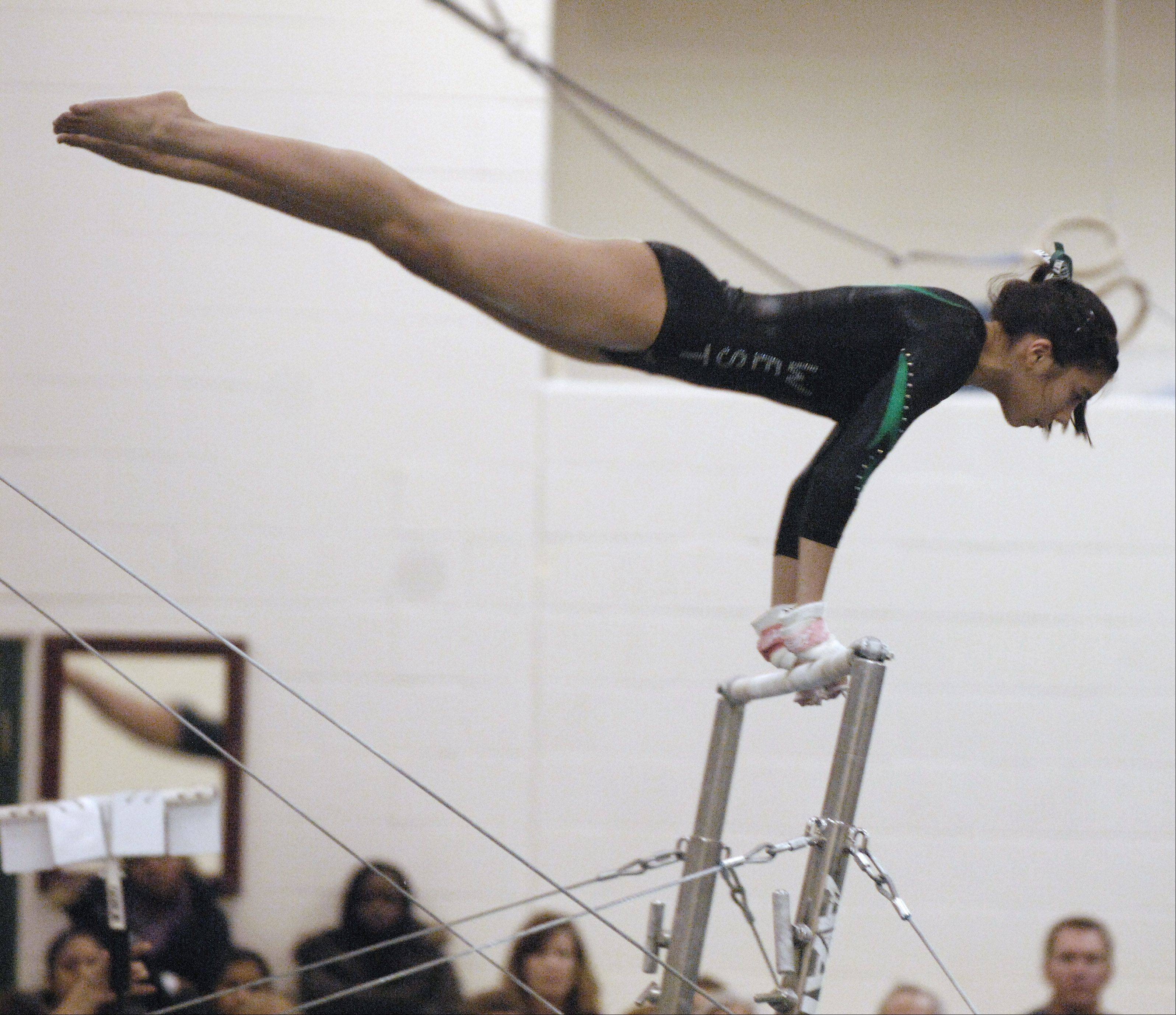 Abbie Garchitorena of Glenbard West performs on the bars during a dual gymnastics meet against Lyons Township in at home in Glen Ellyn.