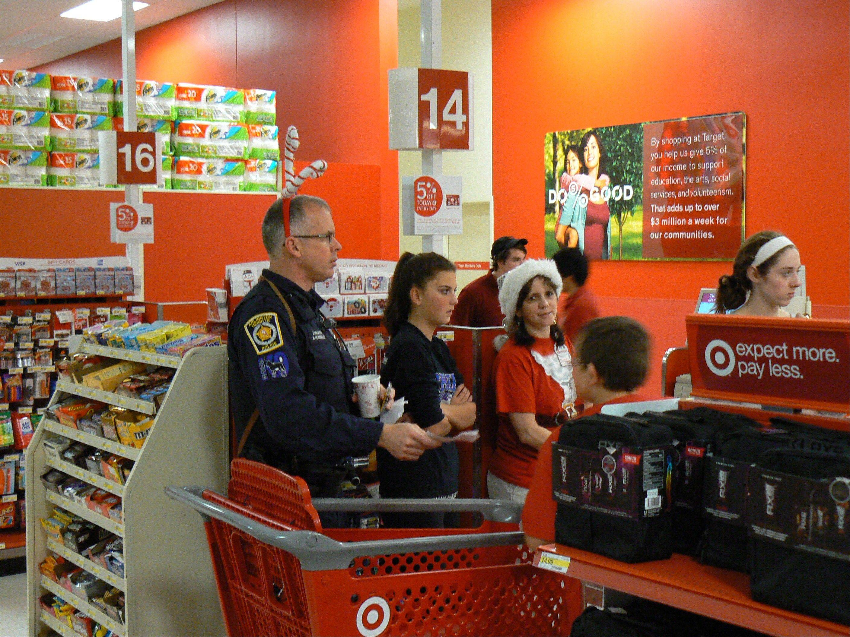 Jim McGrath, K-9 officer, shops with a District 25 student with the help of a Target employee and two members of the Hersey High School freshman basketball team.