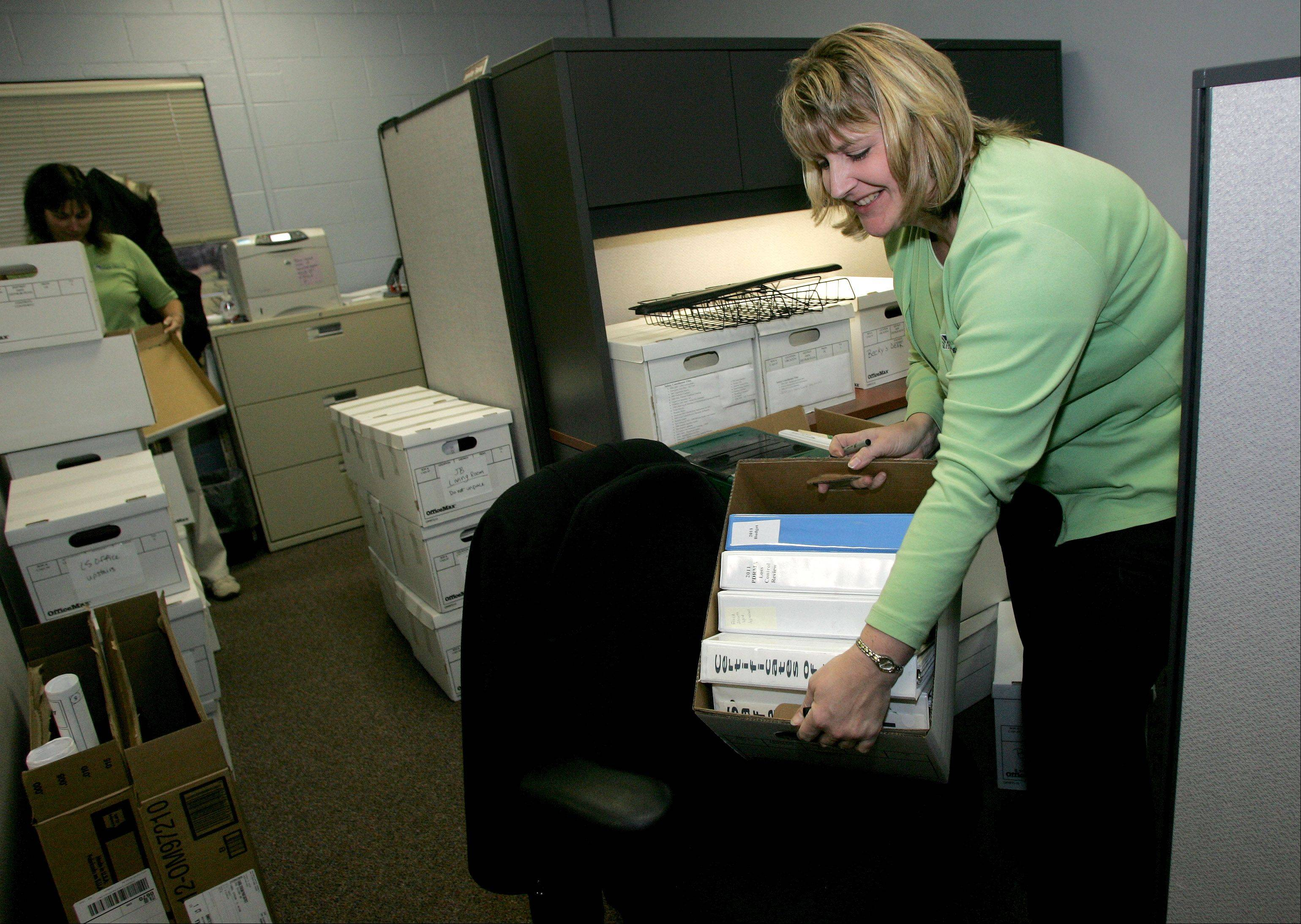 Becky Cooper, a safety and administration coordinator for Carol Stream Park District, packs up a box at the Aldrin Community Center, which is scheduled for demolition in the next few months.