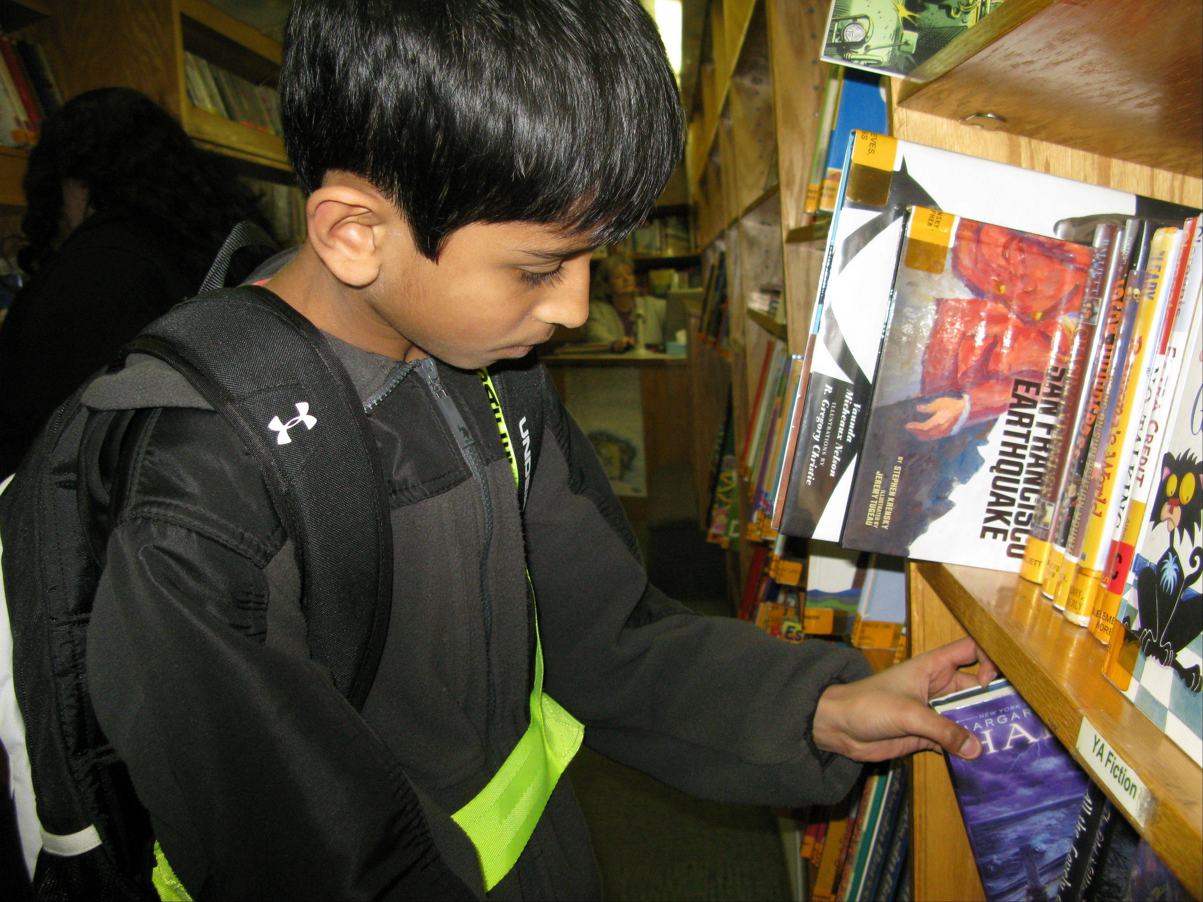 Shiv Patel, fifth-grader at Devonshire School in Des Plaines, checks out the children's fiction collection in the Des Plaines Public Library's bookmobile for the last time.