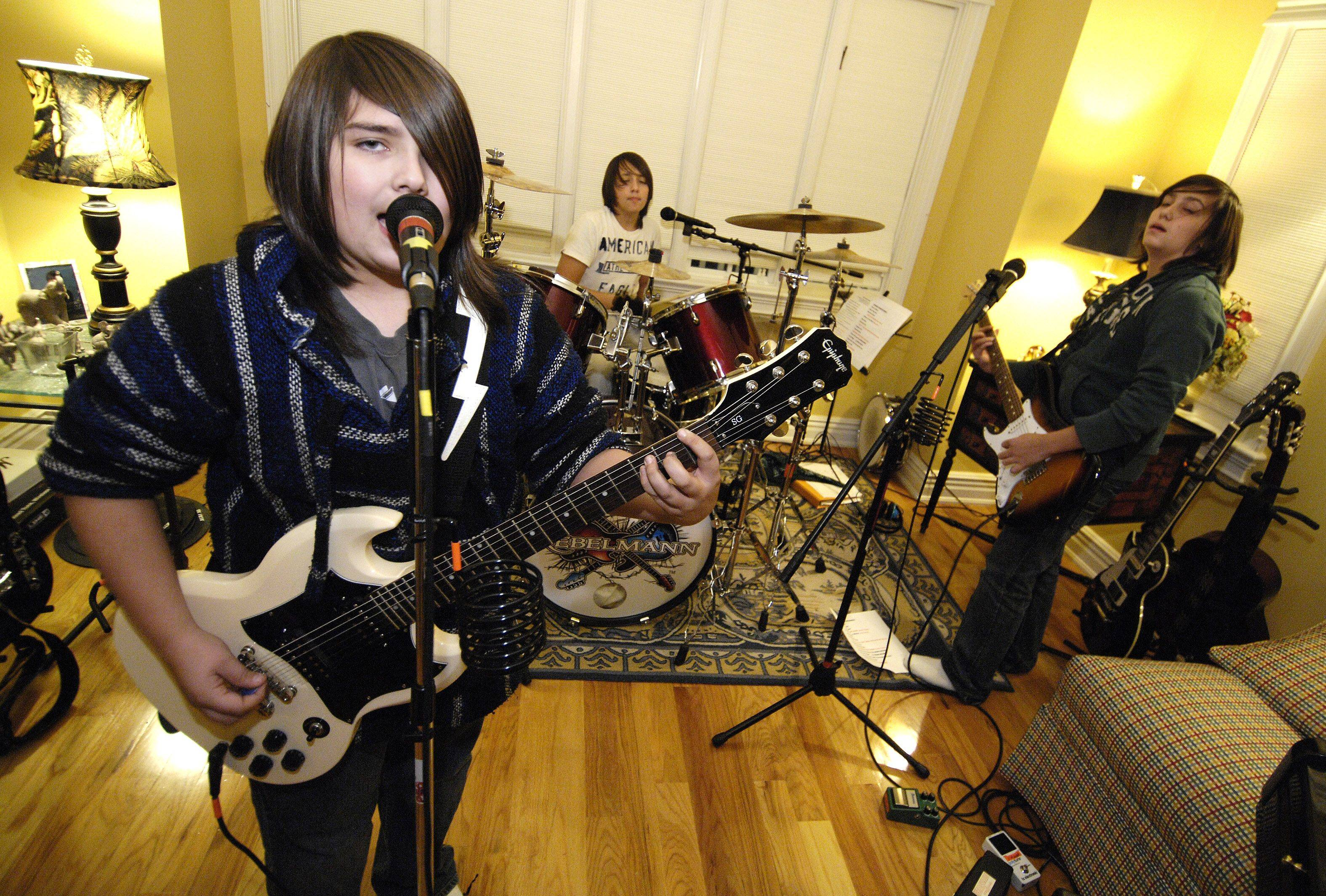 The lead singer of Rebelmann, Clayton Mann, 12, practices with his 14-year-old twin brothers, Johnathon (on guitar) and Bryce (on drums.)