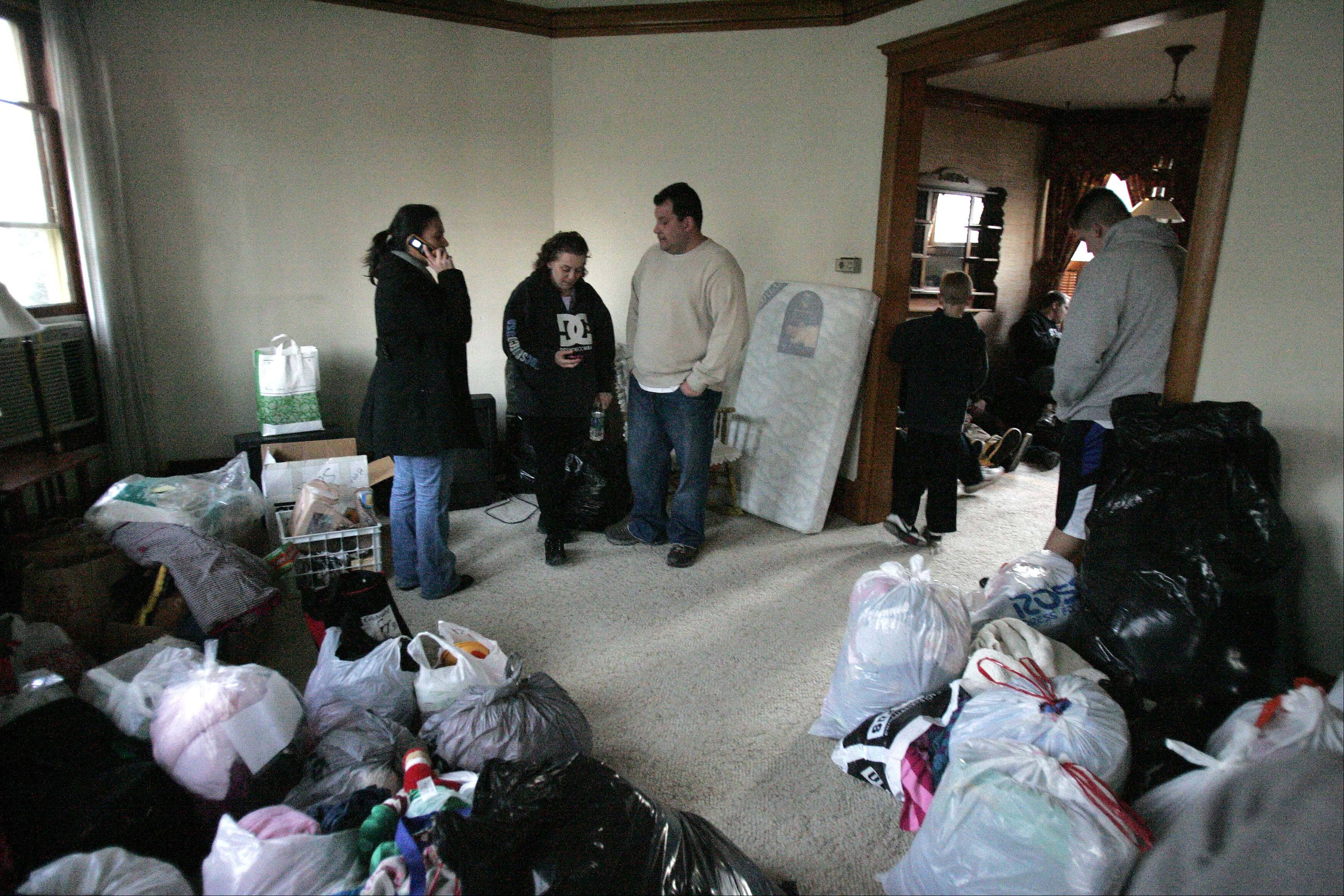 Amy Warner, left, talks to Michelle Konecki and Jack Fisher among a floor filled with donated items. St. Thomas More Church in Elgin amassed bags full of supplies to help the family get back on its feet. And members of the St. Edward High School football team and other students helped move the family into its donated digs.