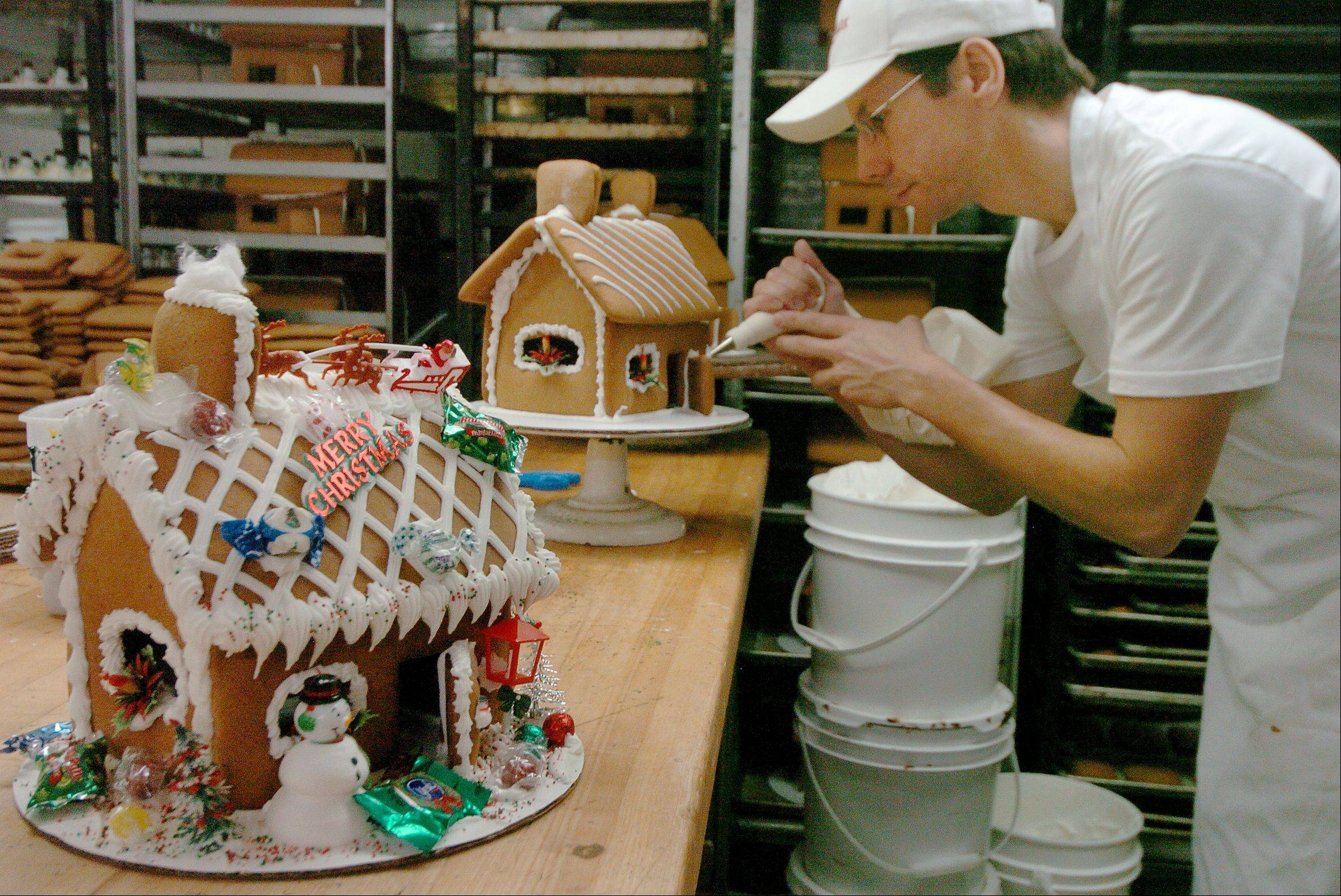 Cake decorator Chris Kowalczyk puts the finishing touches on one of 200 gingerbread houses at Central Continental Bakery in Mount Prospect.