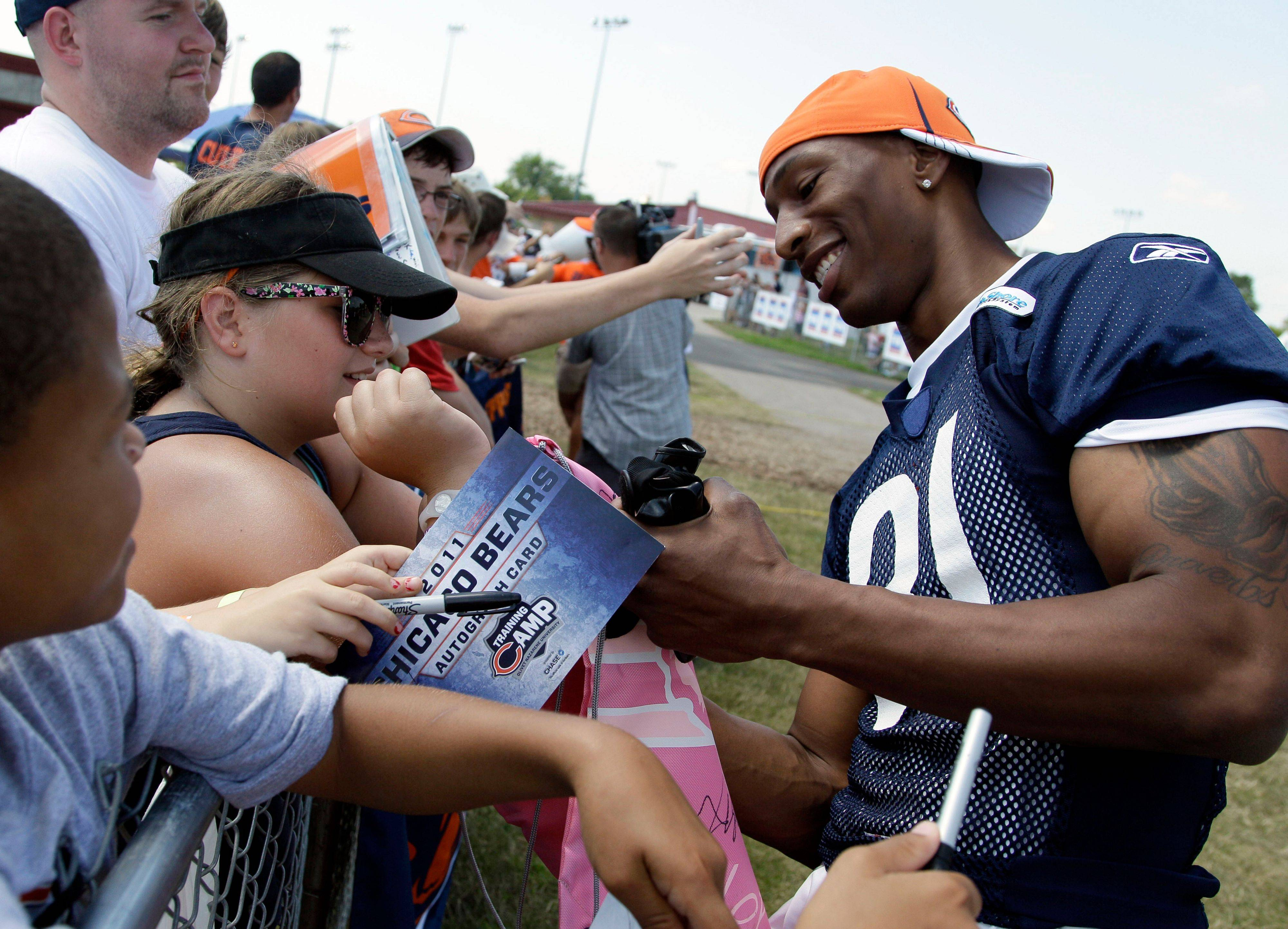 Chicago Bears wide receiver Sam Hurd, right, signs autographs for fans before NFL football training camp in July at Olivet Nazarene University in Bourbonnais, Ill.