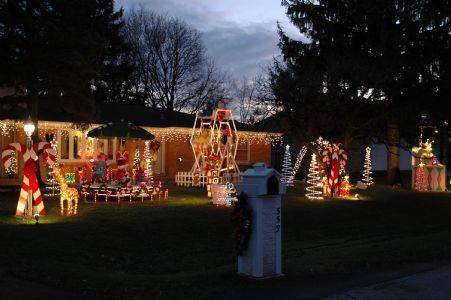 "Nestled in Roselle at 559 W. Ardmore Ave., you'll find Santa's Toyland complete with a working Ferris wheel filled with Sesame Street characters at the Scow house. The Scow display also includes a moving ""bicycle carousel"" with dolls. Santa can be found waiving under the lit gazebo next to a giant jack-in-the-box. Scattered about are presents, candy canes and toy soldiers."