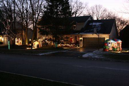 The Clark family keeps the Nativity scene front and center at their home at 1260 Redfield Road in Naperville. In a grove of trees off to the left, Santa, Mrs. Claus and a few of their reindeer greet passers-by. The Santa Train off to the right has a working merry-go-round filled with a few of Santa's friends. Two Christmas trees, decorated with a host of ornaments and colored lights, can be seen from the two bay windows. All windows, front porch, and garage are outlined in white lights, with wreaths and garland. The front porch is also decorated with an Angel, a small Santa, and a Dalmatian dog dressed for the holidays, who spends most of his time rocking in the chair. In addition, each street in the neighborhood decorates their parkway trees with a different theme, Jeannette Clark says.