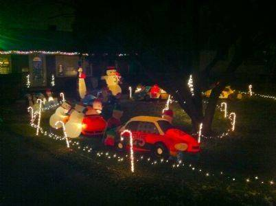 A racing themed yard at the Carlson home displays five unique cars and pit crews, snowman flagman, penguin trophy holder and penguin spectators for the Santa 500 at 1505 Burlington Ave., in Lisle.